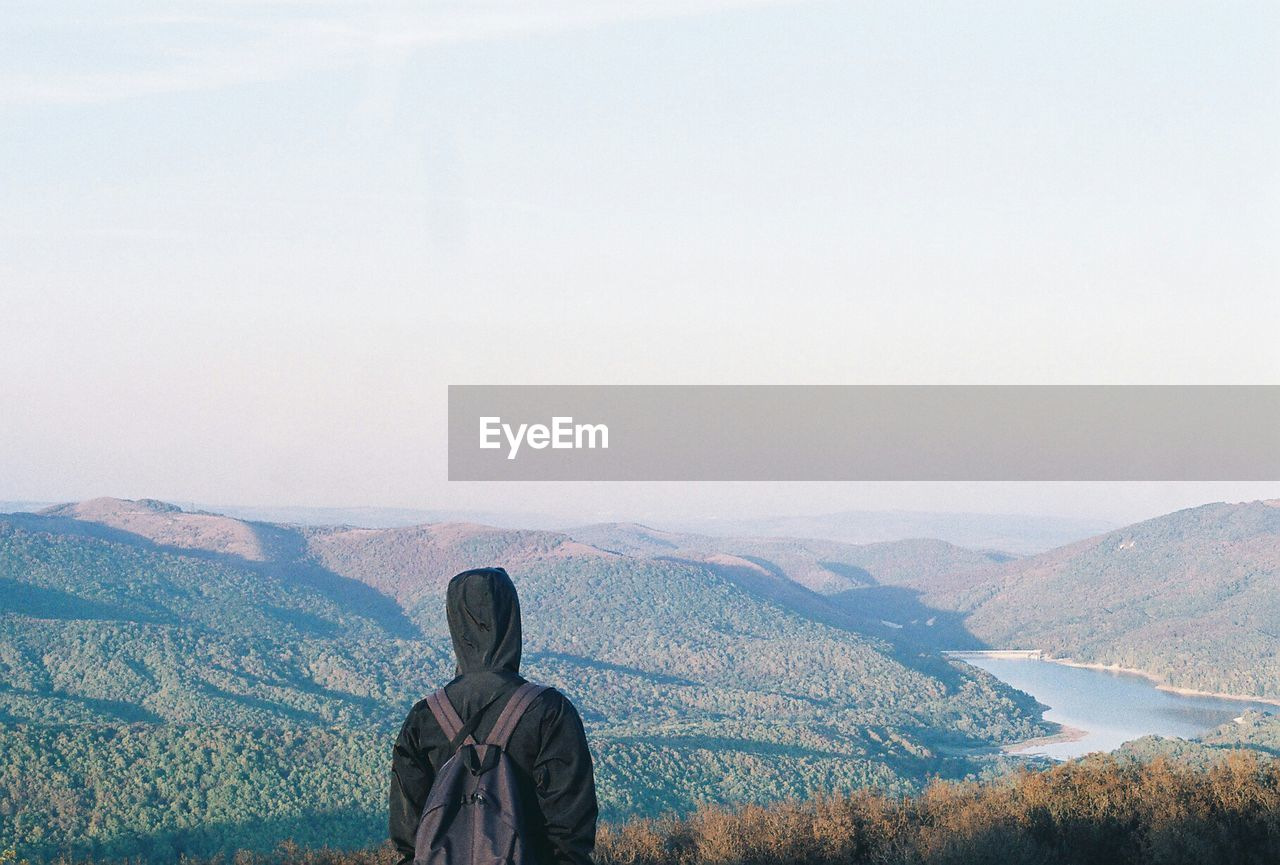 Rear view of person standing by mountains against sky