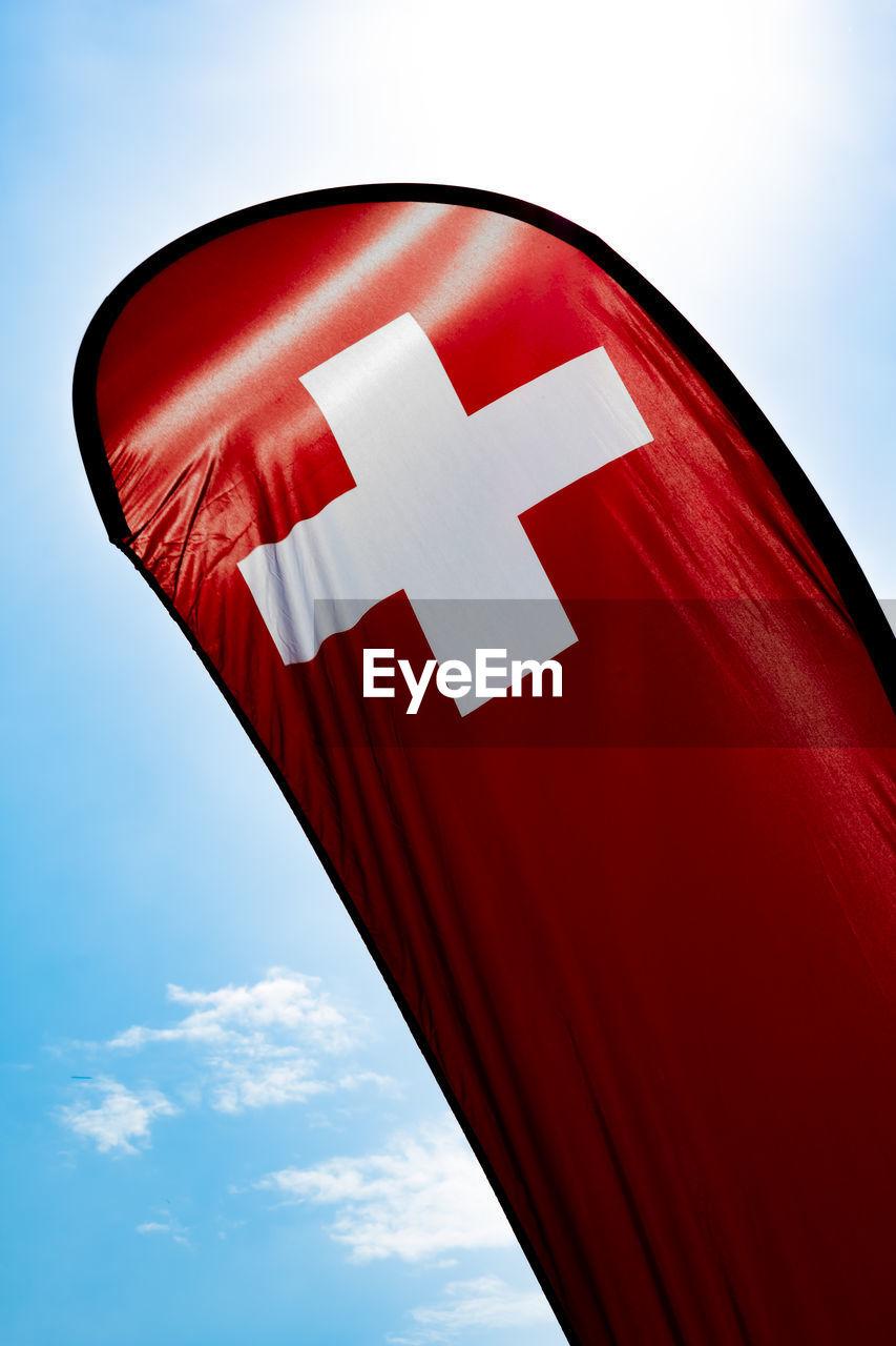 Low Angle View Of Swiss Flag Against Sky