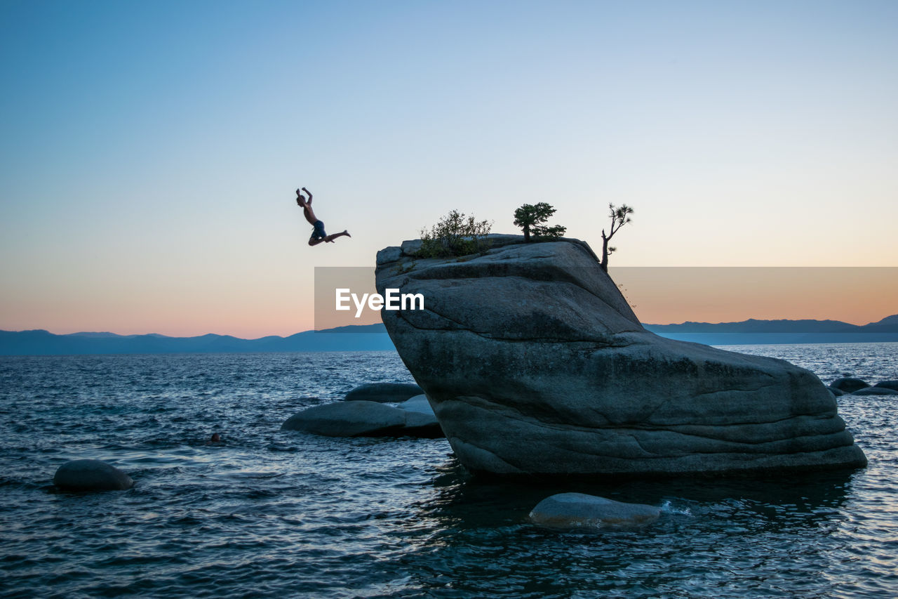 Man Jumping Off Of Rock By Sea Against Clear Sky