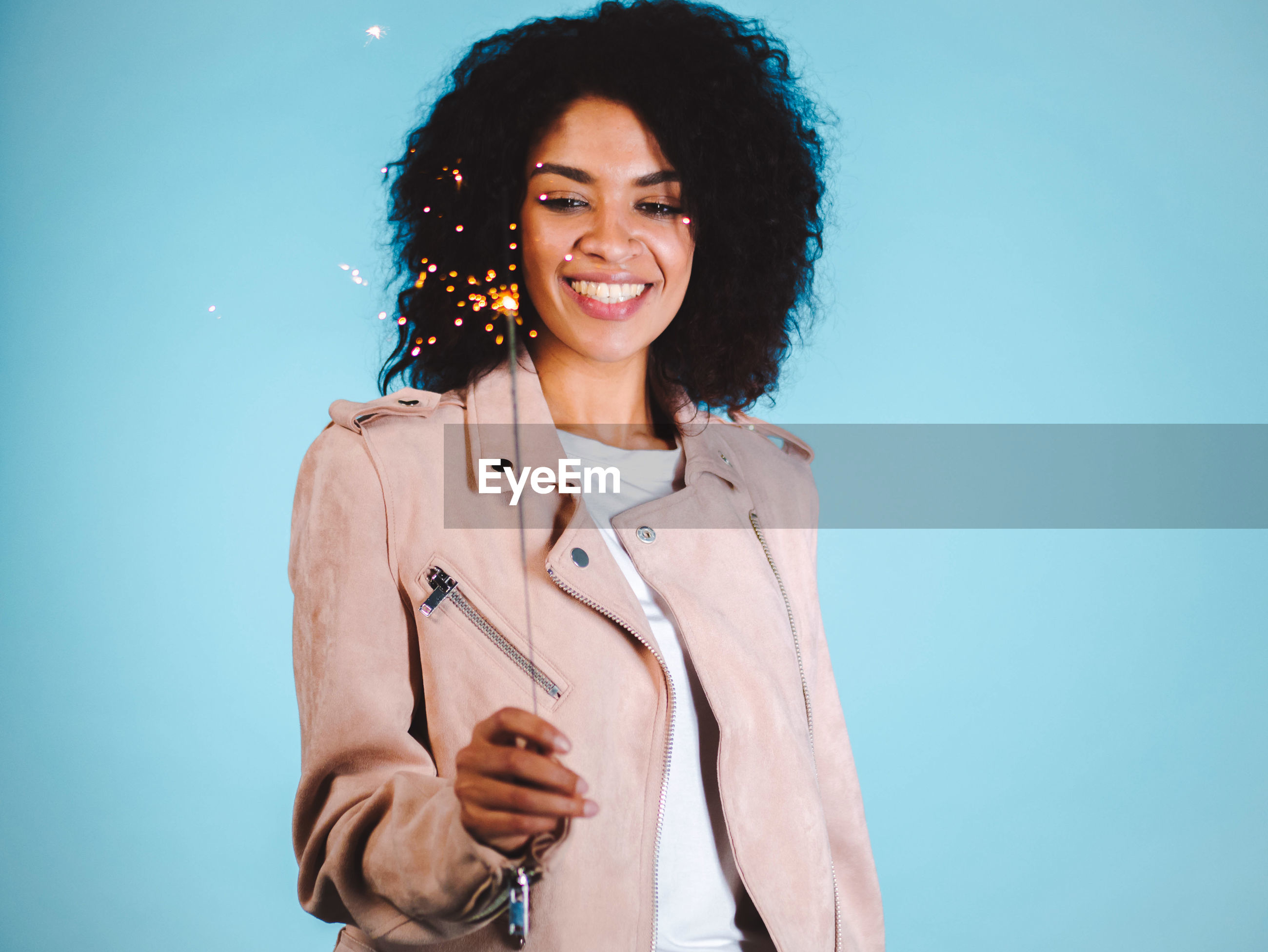 Smiling young woman holding sparkler while standing against blue background