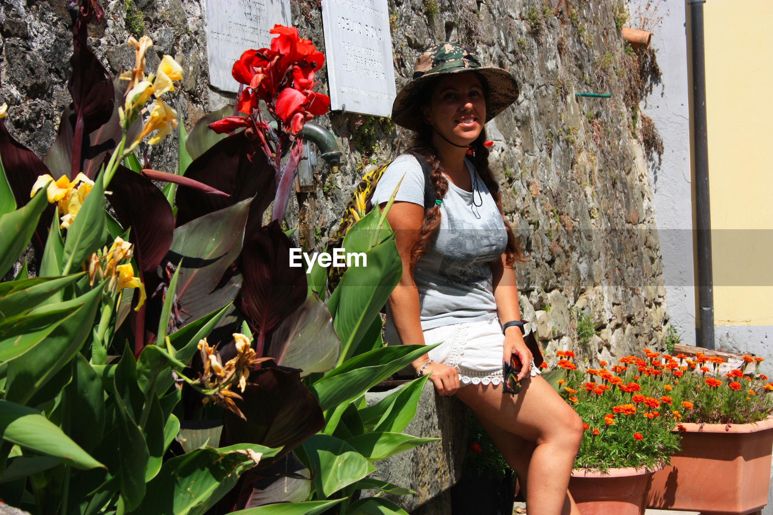 WOMAN SITTING ON PLANT
