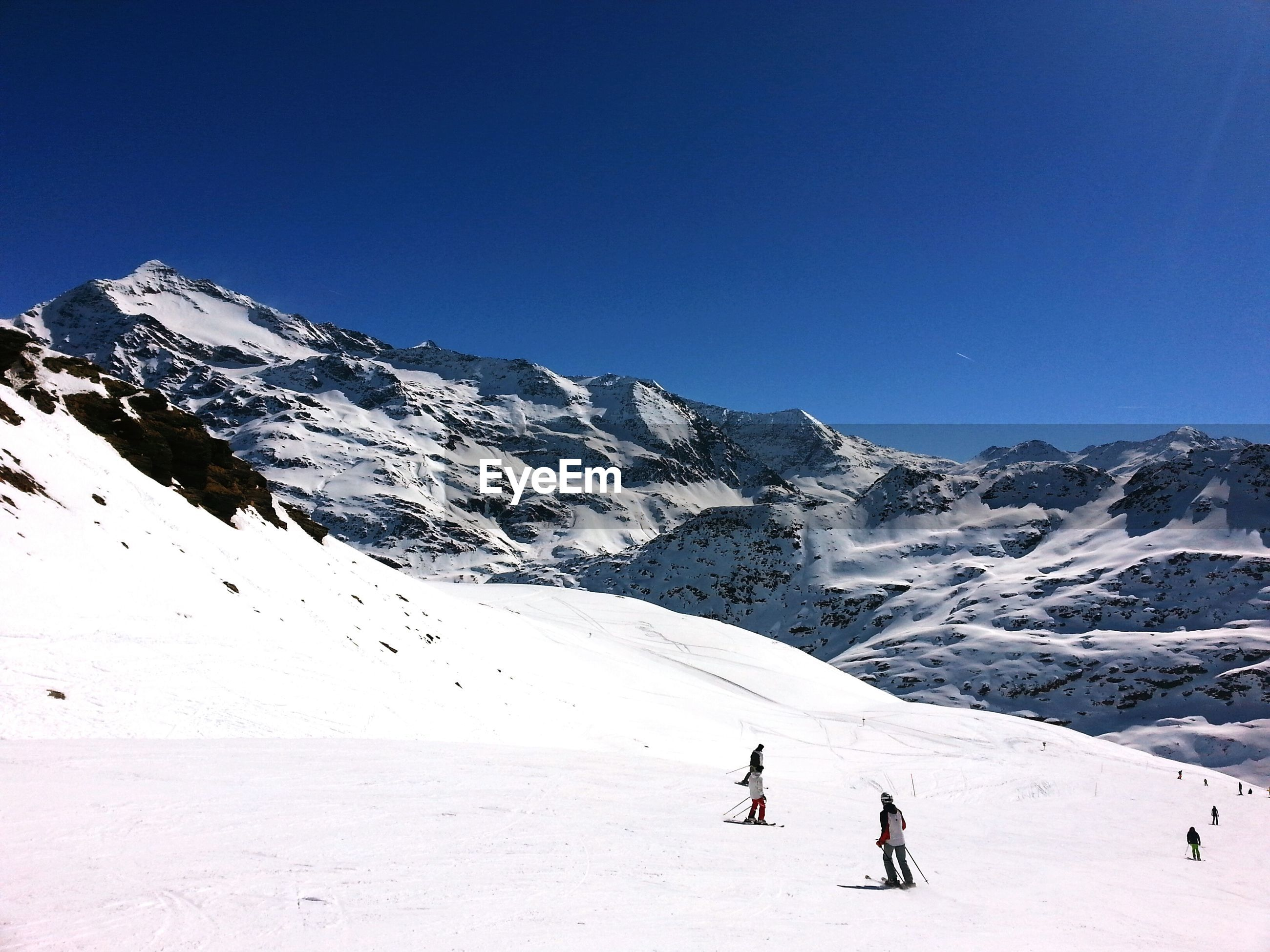 People skiing on snow covered landscape against clear sky