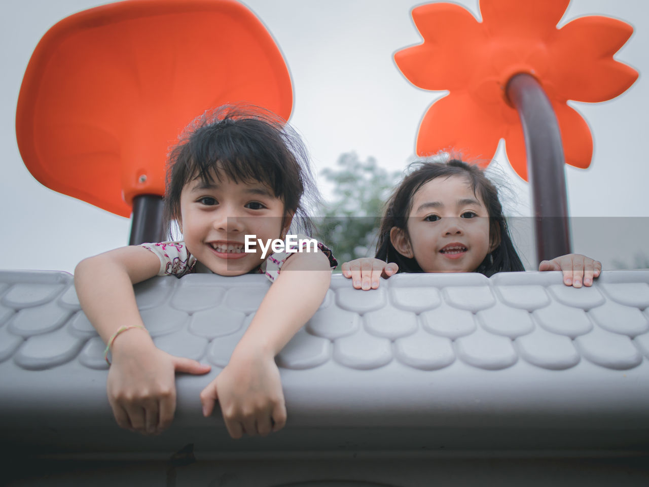 Low angle portrait of cute sisters lying on outdoor play equipment against sky in park