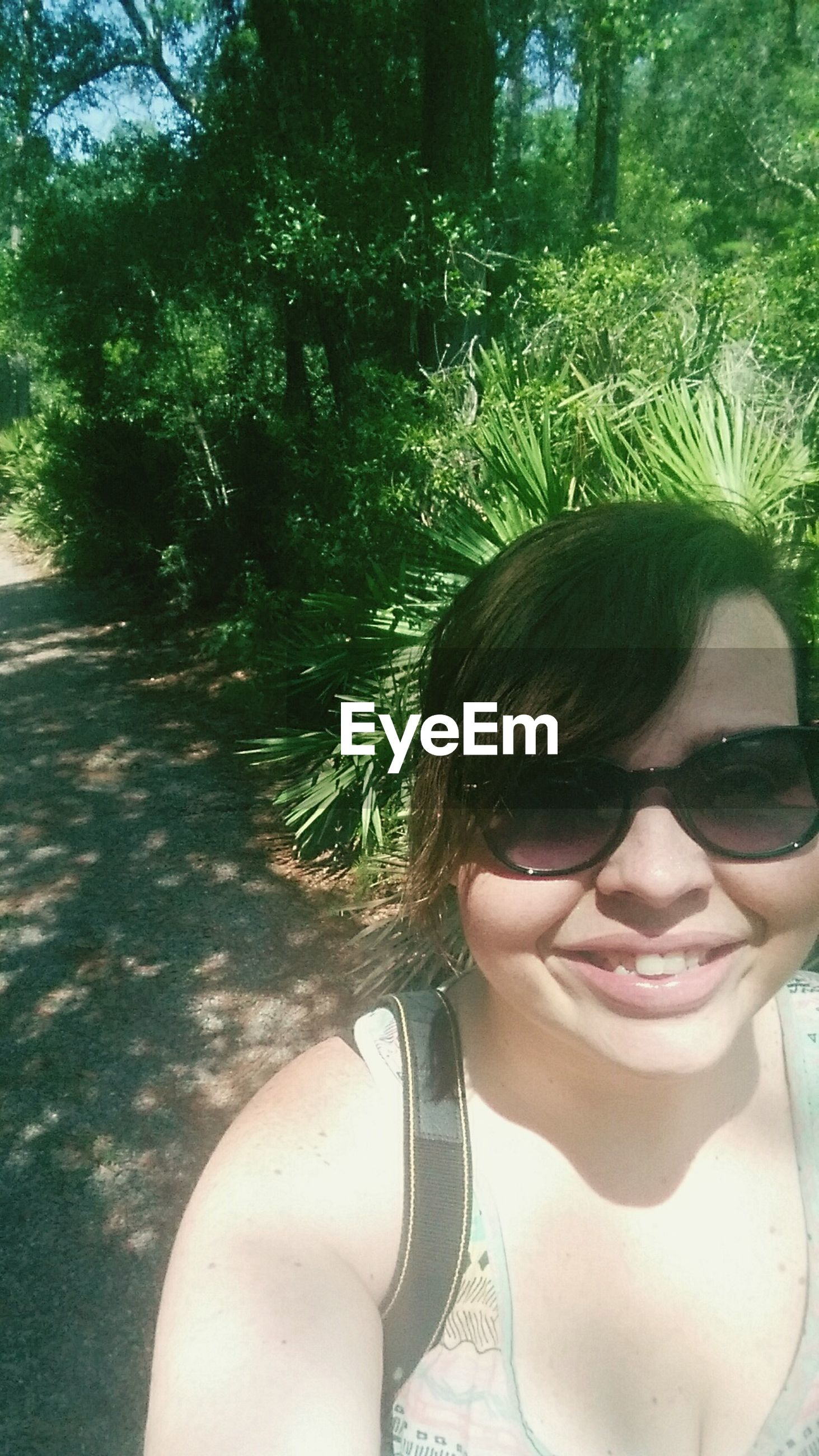 tree, person, lifestyles, leisure activity, young adult, looking at camera, park - man made space, young women, portrait, casual clothing, headshot, front view, day, smiling, sunlight, sunglasses, outdoors, growth