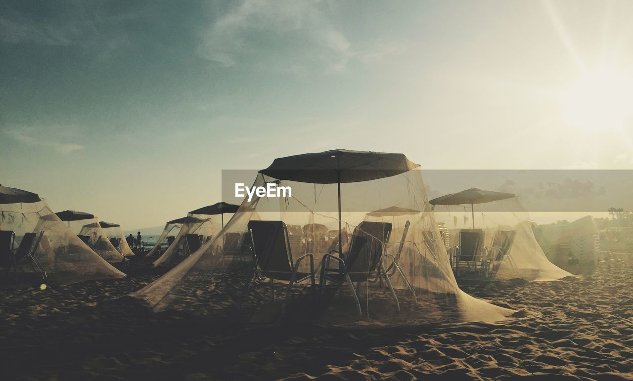 Chairs And Parasols Covered With Mosquito Nettings At Beach Against Sky