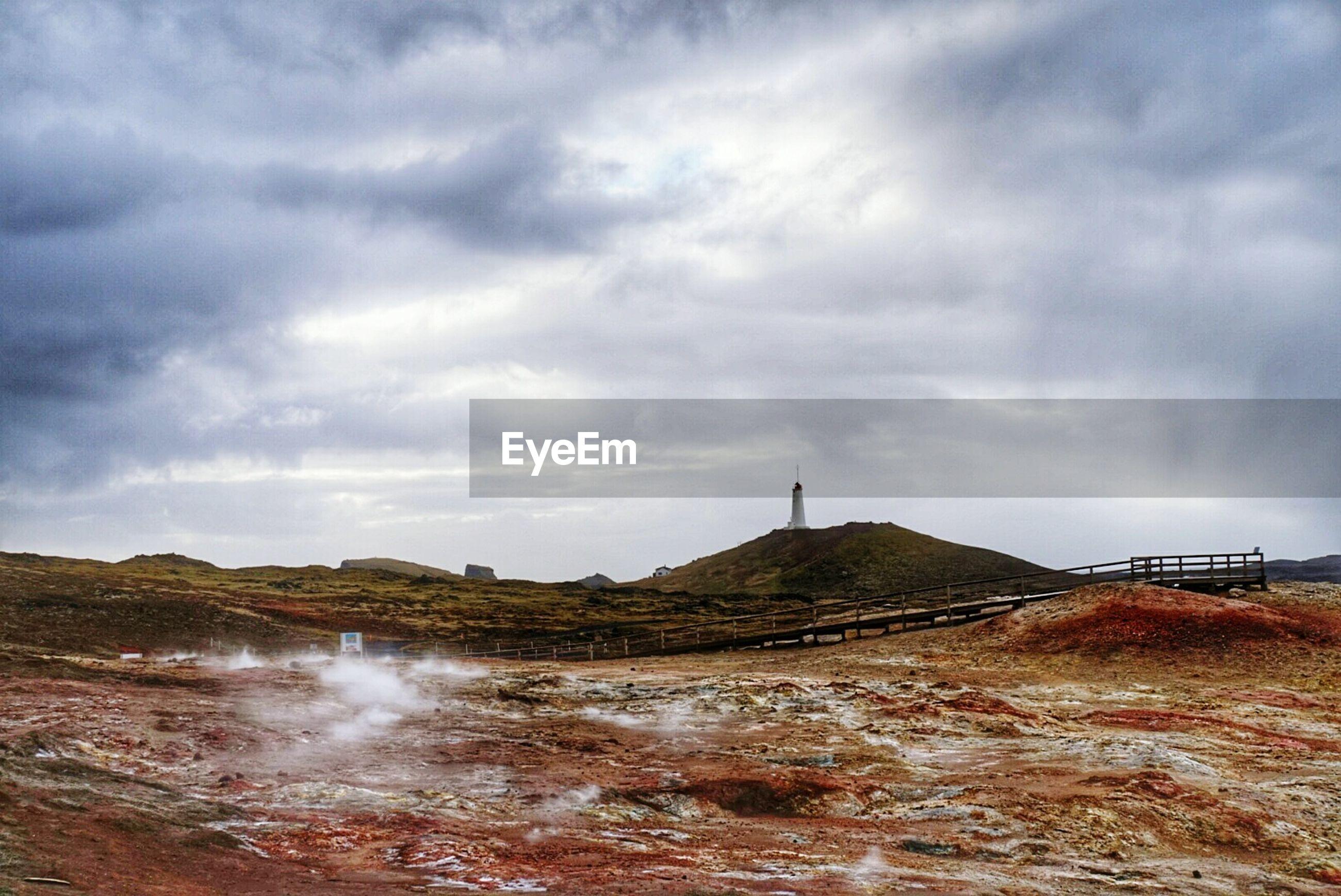 Hot springs at reykjanes peninsula against cloudy sky