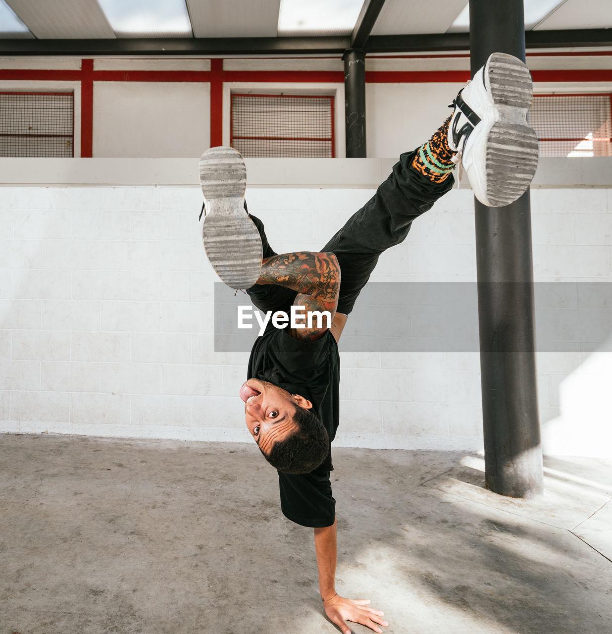 FULL LENGTH OF MAN SKATEBOARDING ON FLOOR