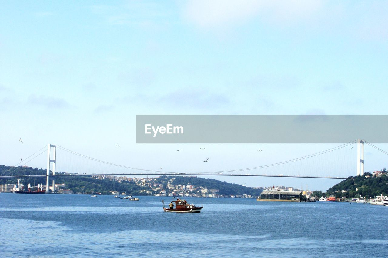 Boat sailing in marmara sea by suspension bridge against sky