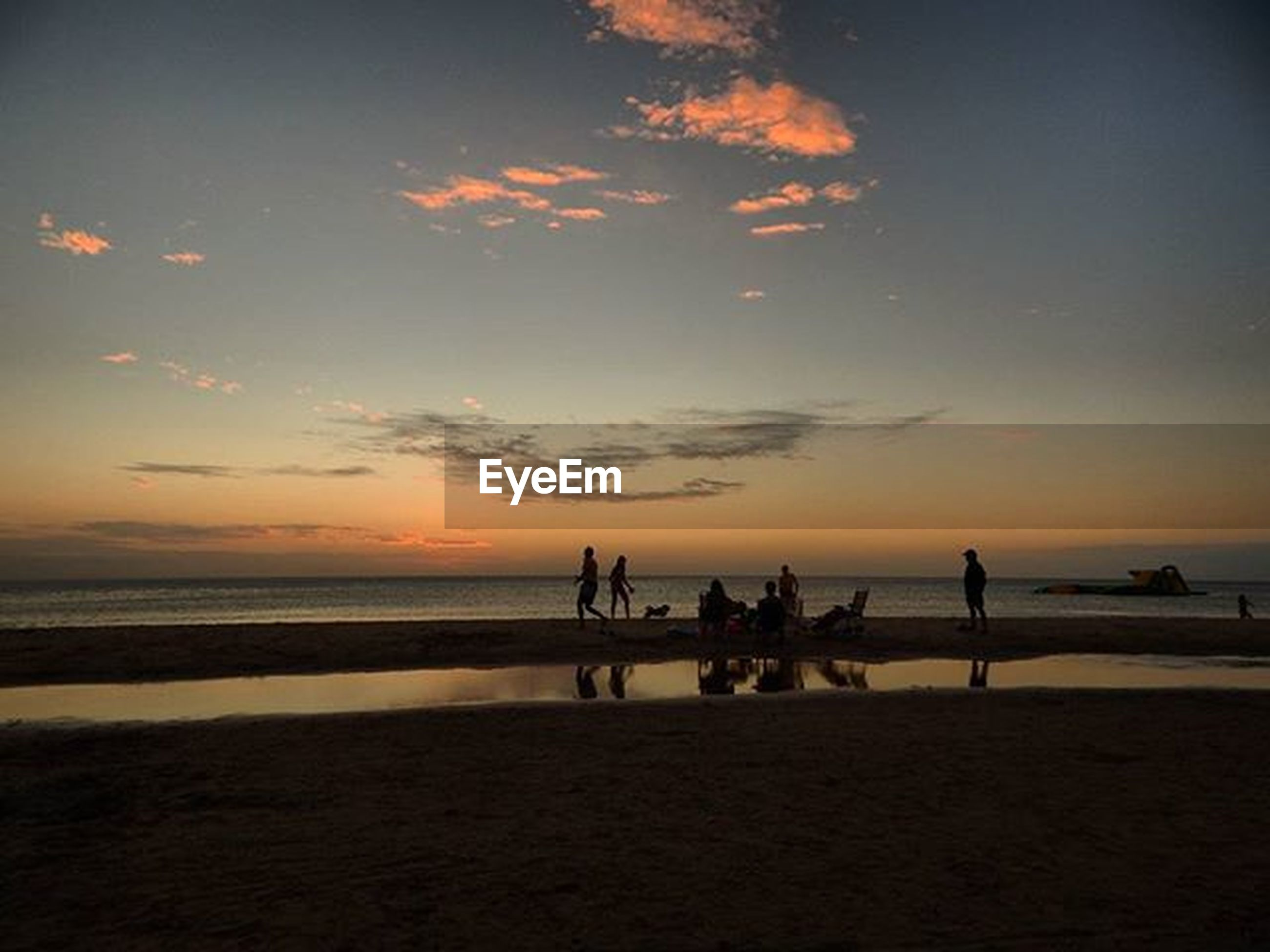sunset, sea, silhouette, beach, horizon over water, water, sky, scenics, orange color, tranquil scene, beauty in nature, tranquility, shore, idyllic, nature, cloud - sky, medium group of people, incidental people, unrecognizable person