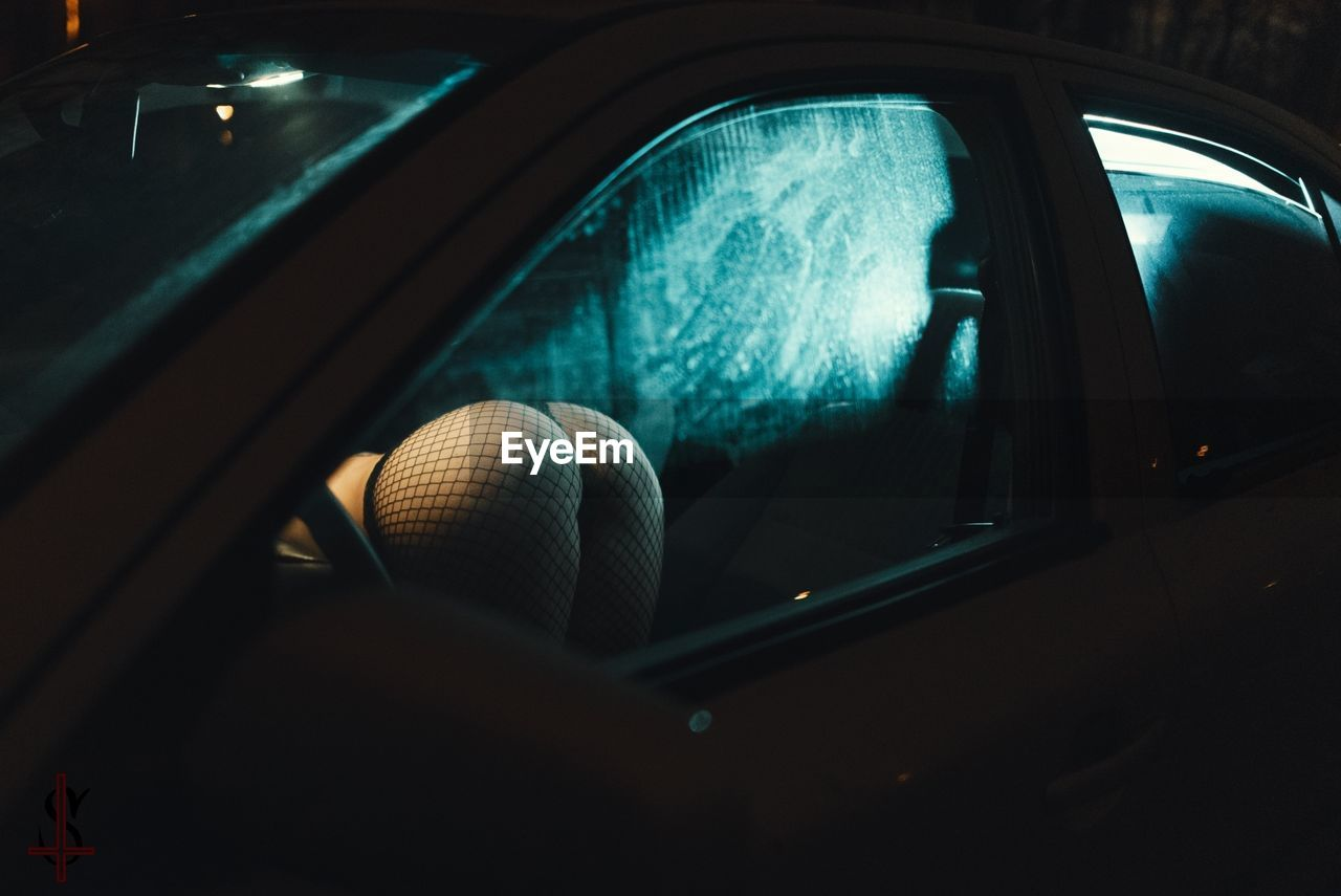 Midsection of seductive woman in car seen through window at night