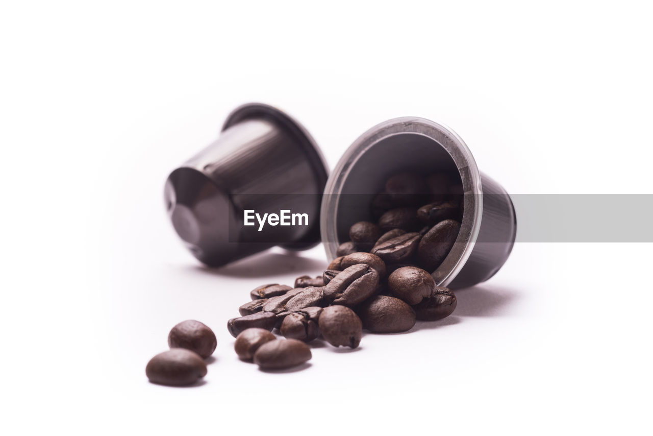 Coffee beans spilling from container against white background