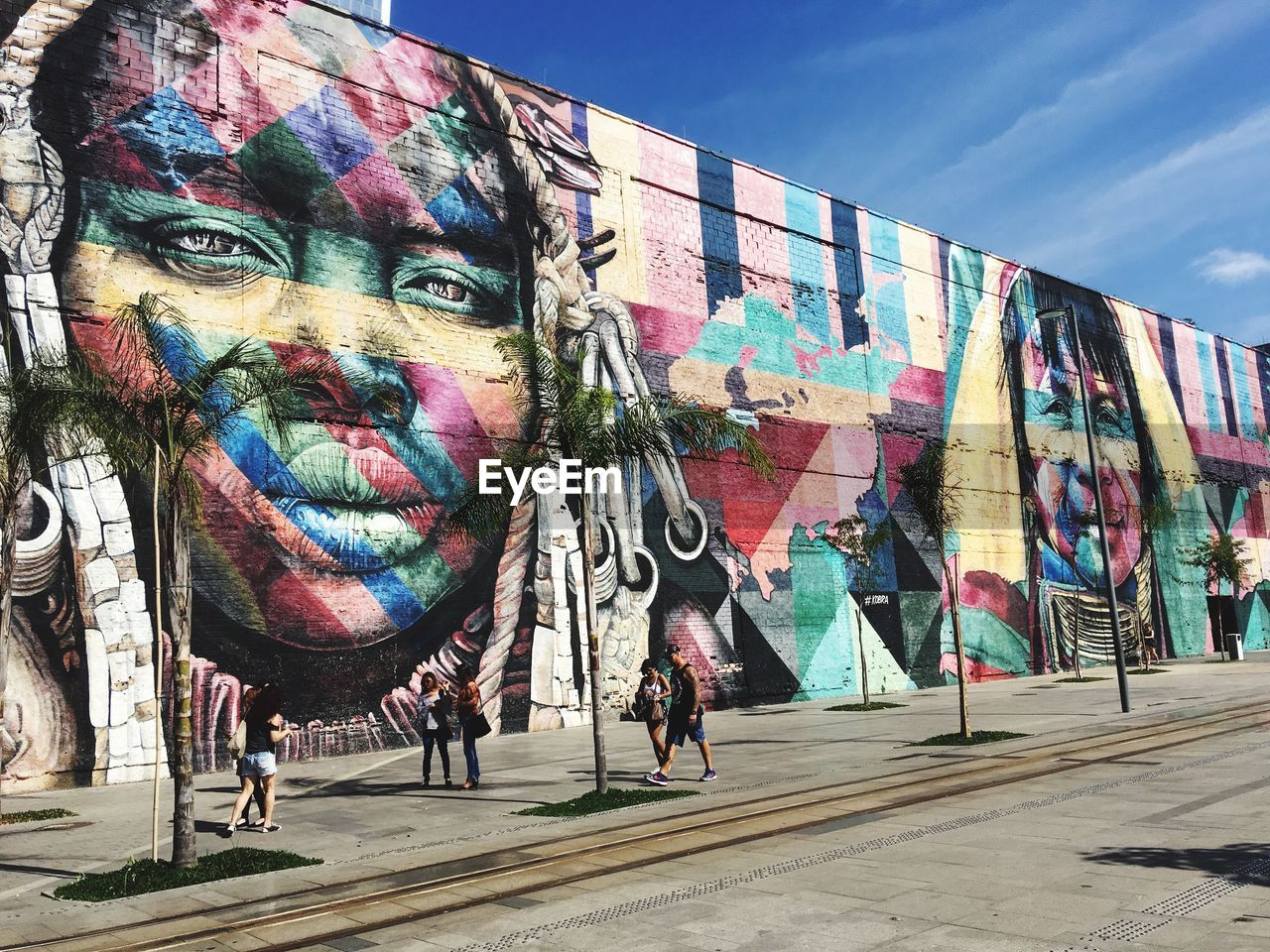 art and craft, creativity, graffiti, representation, multi colored, wall - building feature, built structure, architecture, sky, human representation, day, lifestyles, real people, people, street art, city, building exterior, outdoors, young adult, sunlight, mural