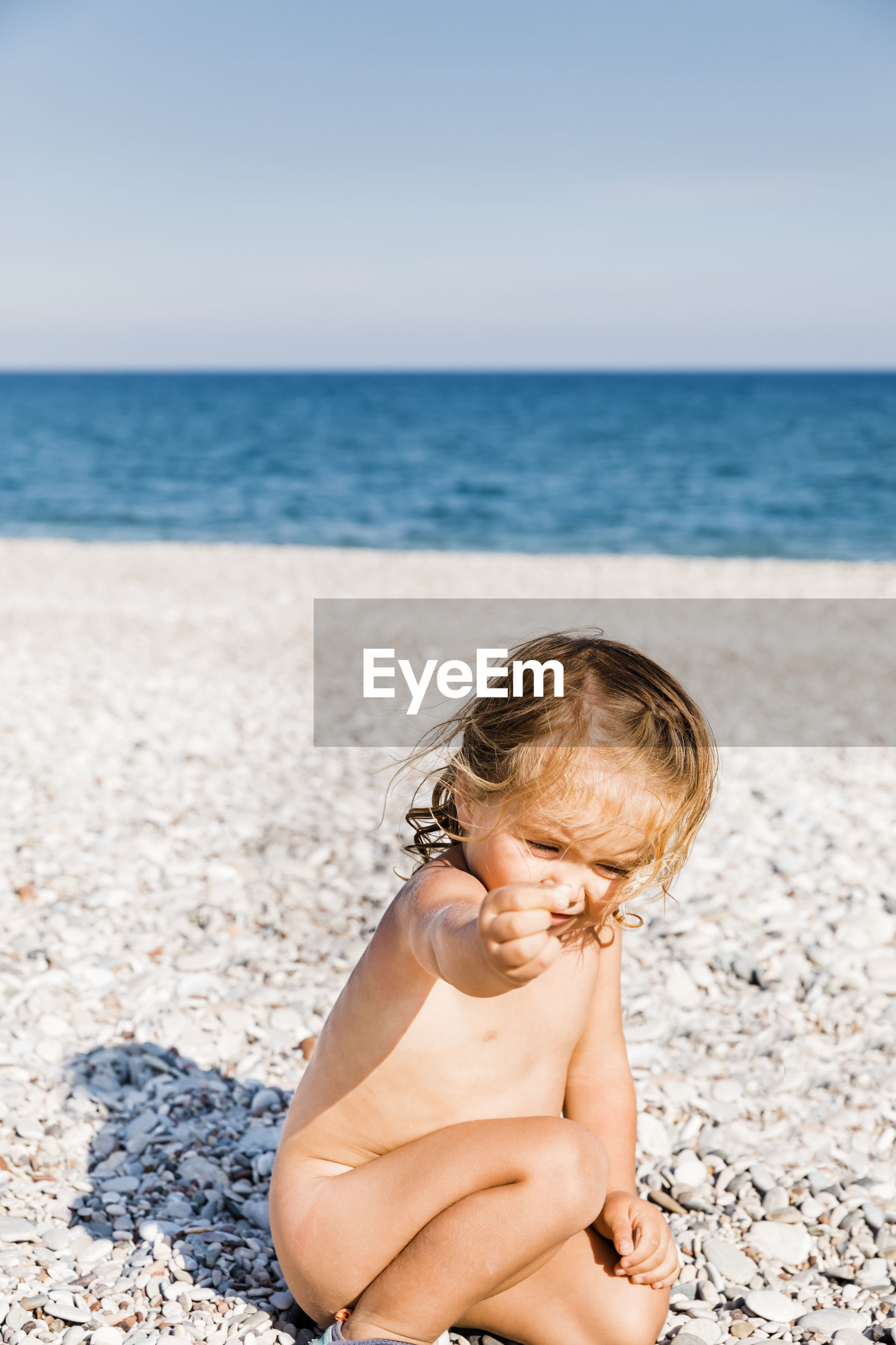 Naked girl crouching on rocks at beach during sunny day