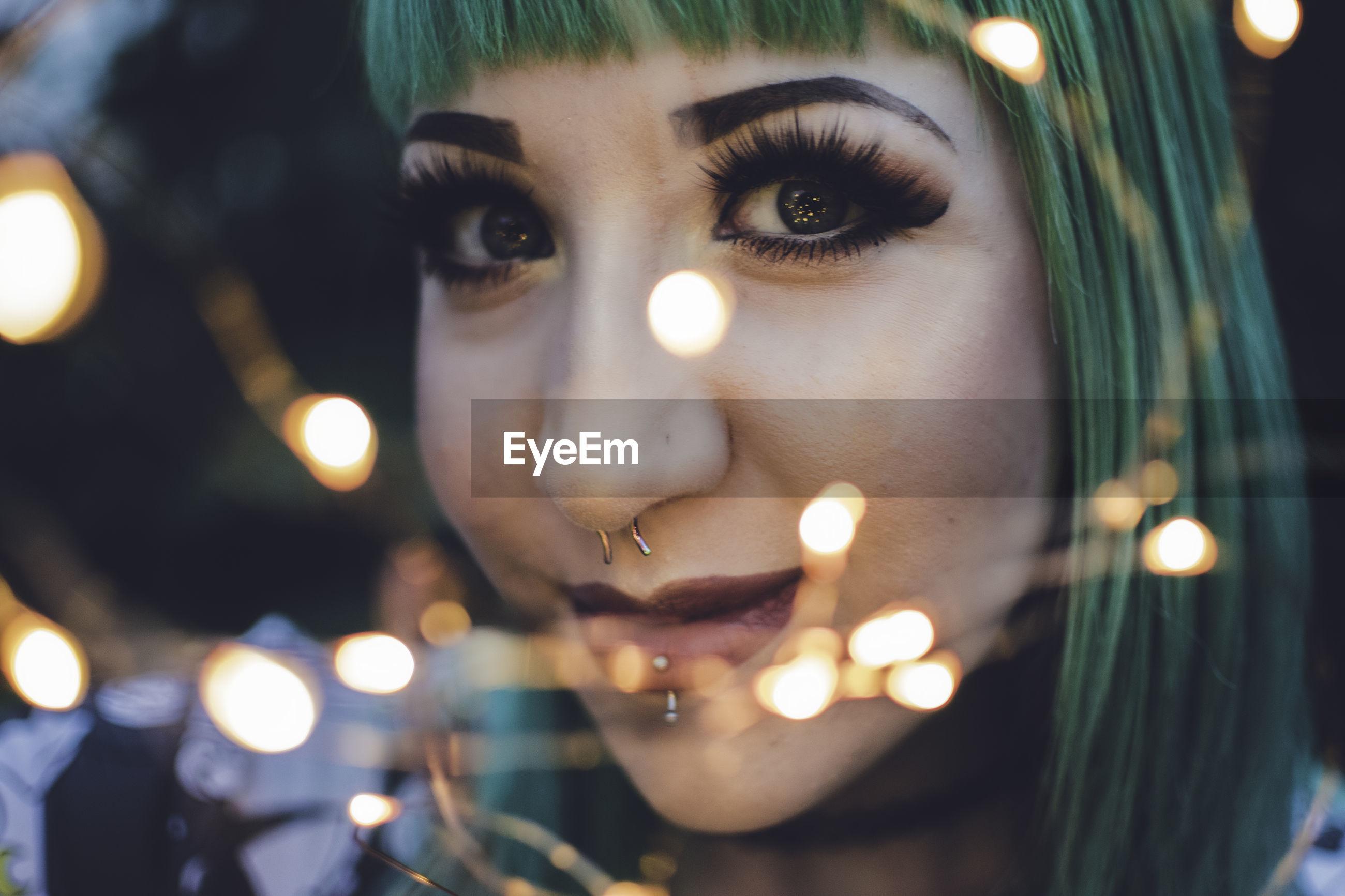 Close-up of illuminated young woman