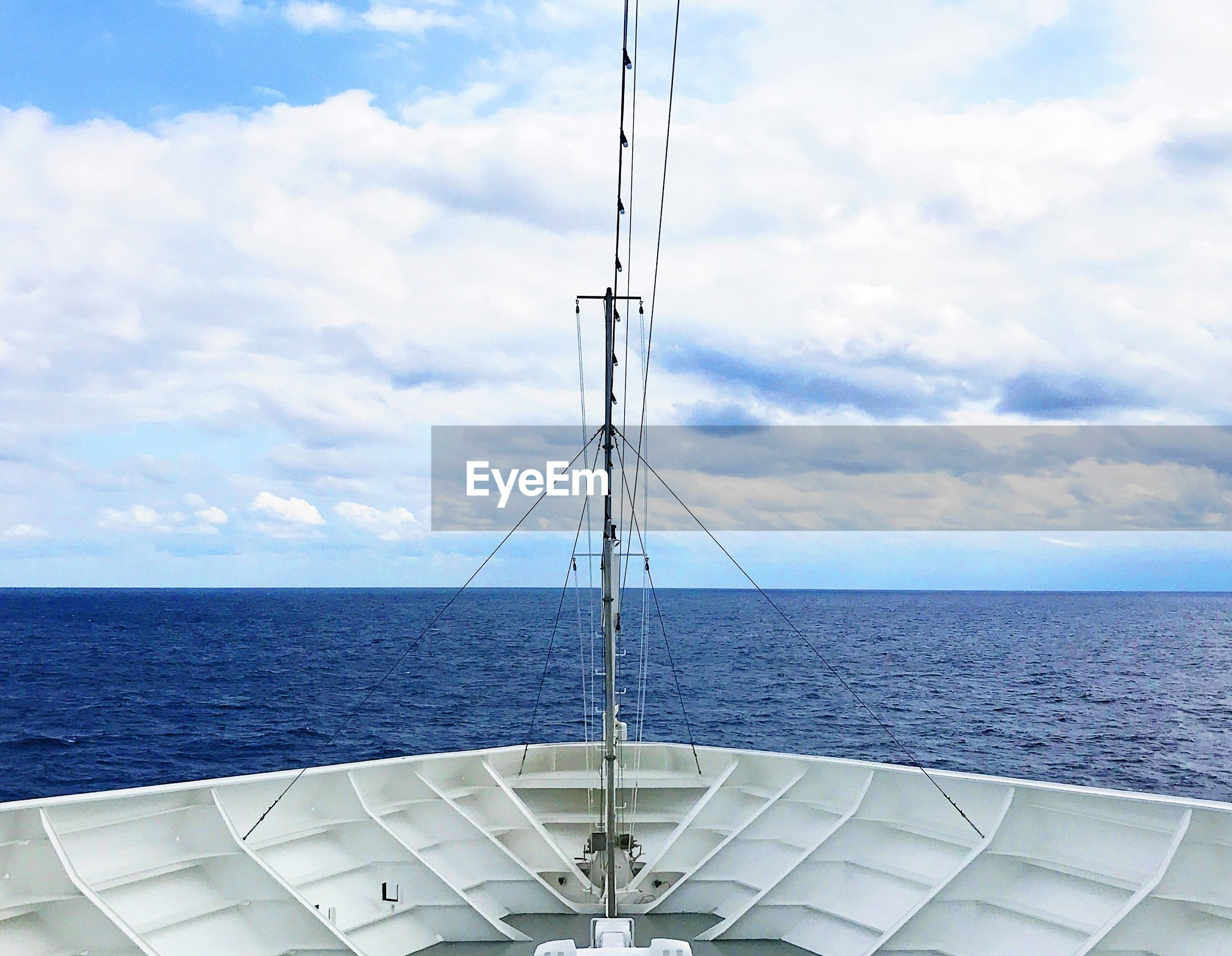 Cropped image of nautical vessel in sea against cloudy sky
