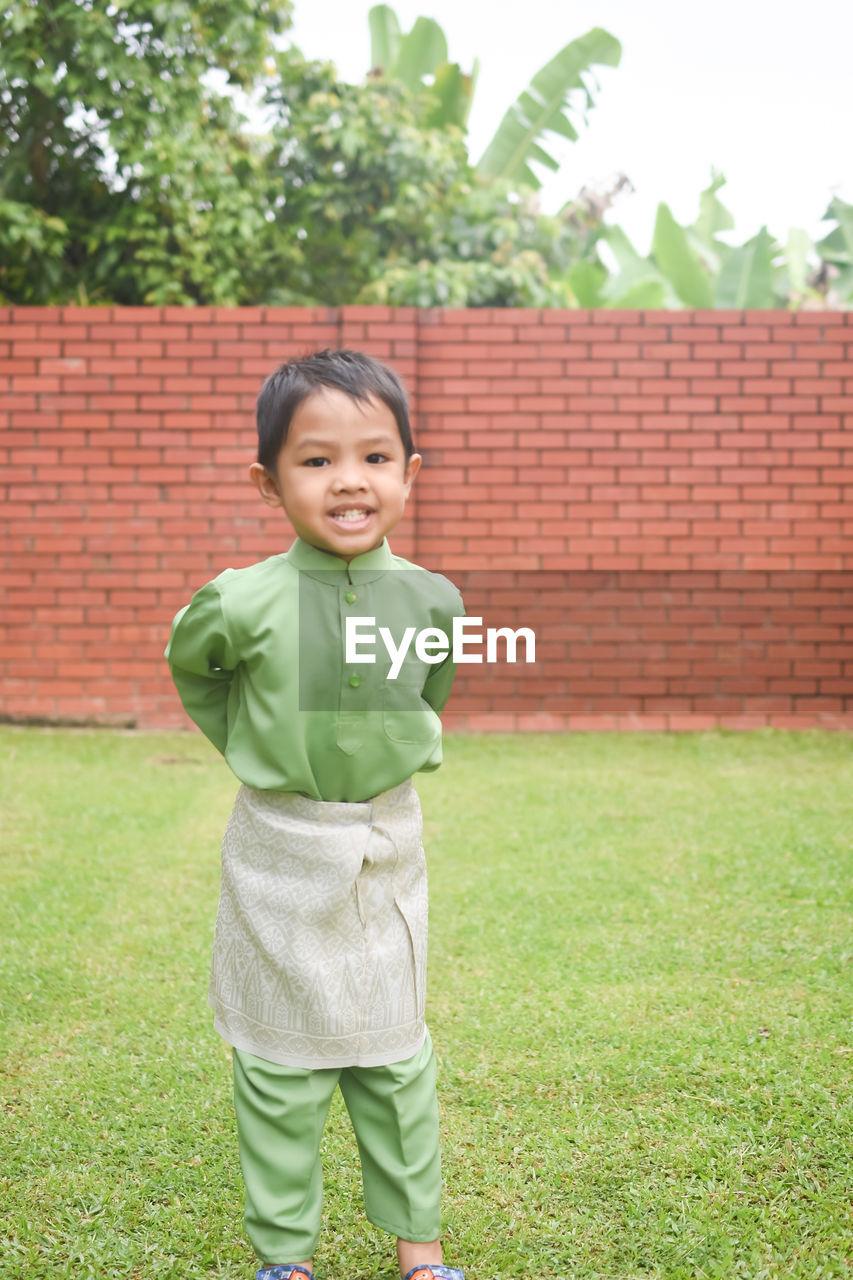 Portrait of boy wearing baju melayu while standing on grassy field