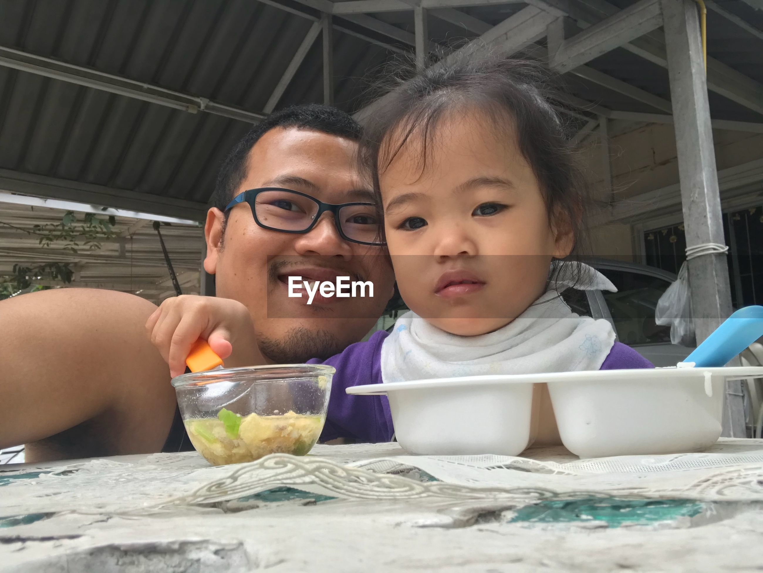 Portrait of smiling man with daughter while eating food