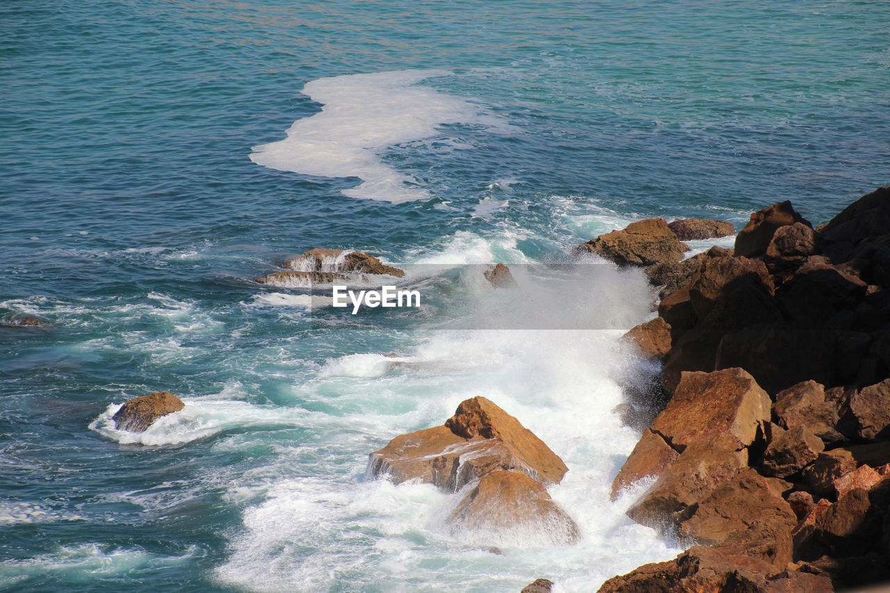 sea, water, rock, motion, beauty in nature, solid, rock - object, sport, wave, nature, scenics - nature, surfing, land, aquatic sport, rock formation, day, high angle view, power, power in nature, outdoors, breaking, hitting