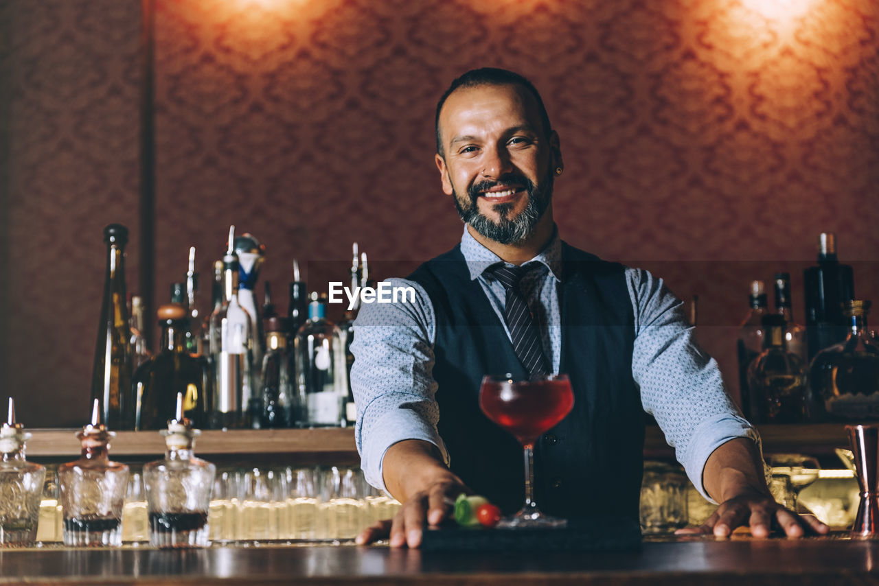 Portrait of smiling mature bartender standing by cocktail on bar counter