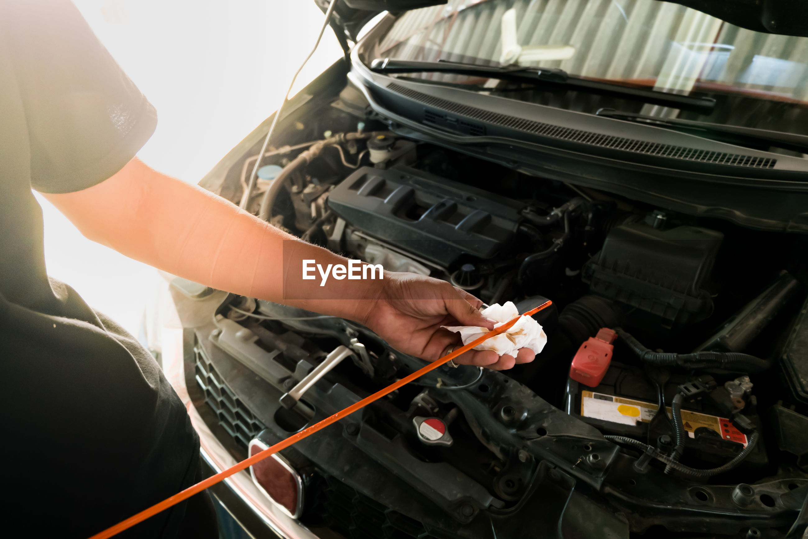 Midsection of mechanic repairing car engine