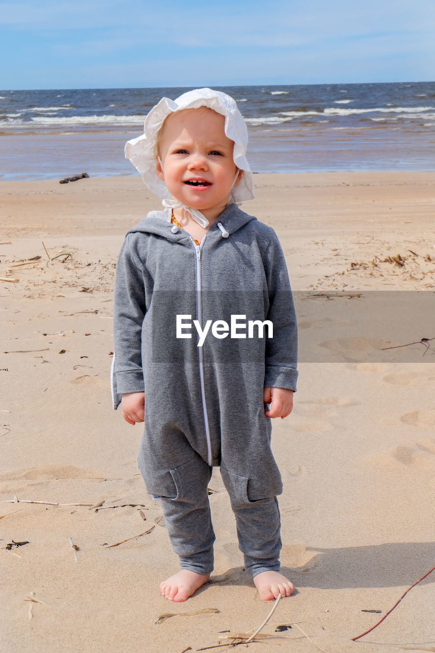 Portrait of cute baby girl standing on beach