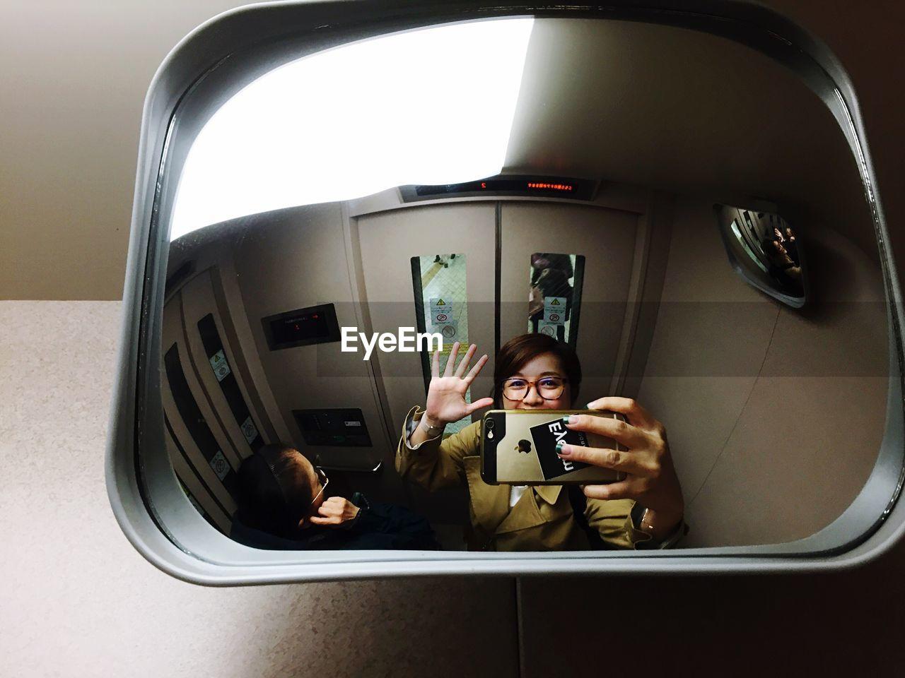 Reflection of woman taking selfie in mirror of elevator