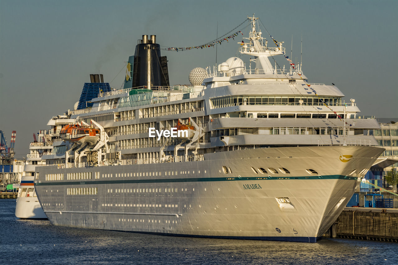 architecture, building exterior, built structure, transportation, mode of transport, nautical vessel, city, outdoors, cruise ship, water, harbor, day, travel destinations, sea, commercial dock, no people, sky, bird, animal themes