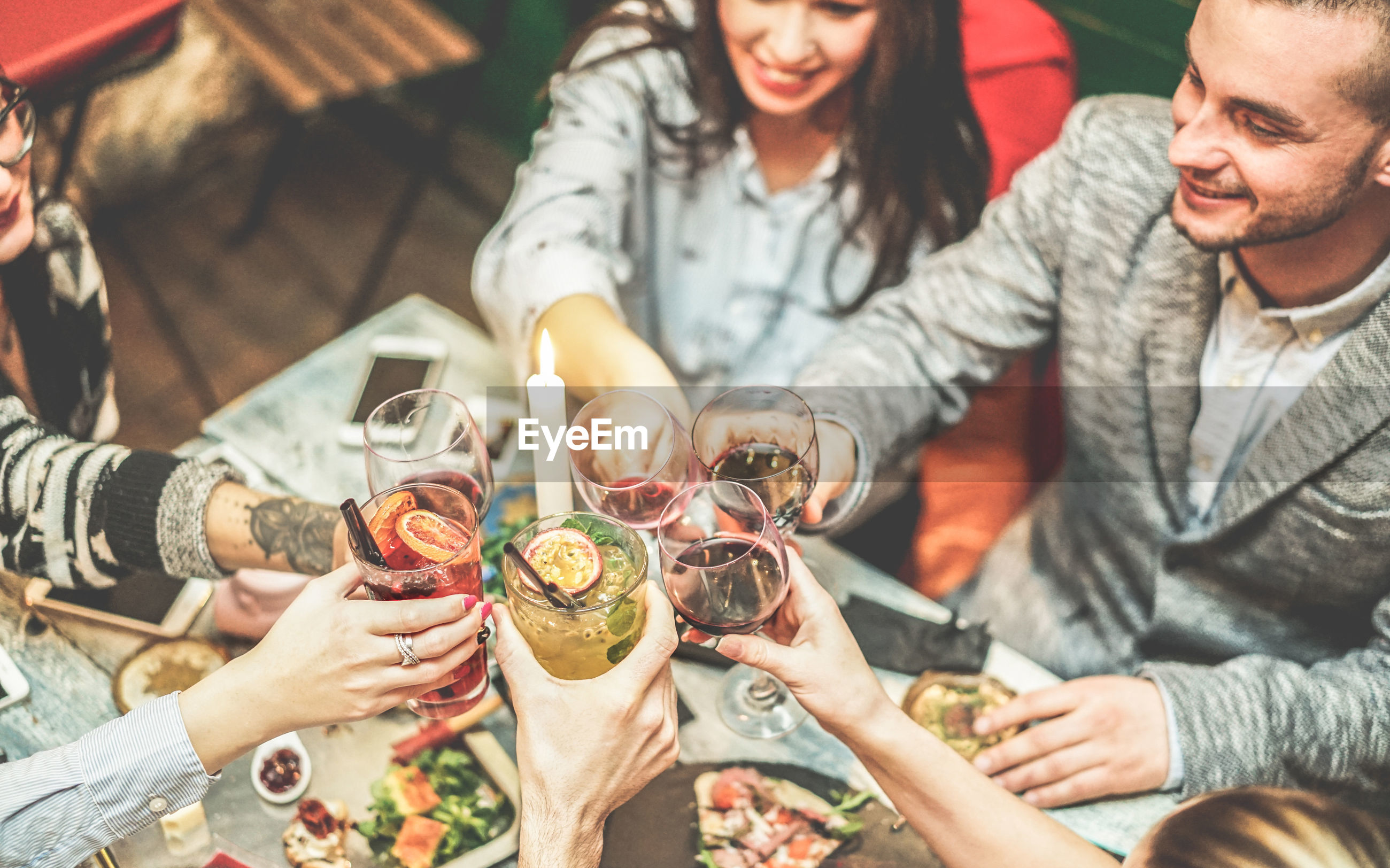 Friends raising toast while sitting in restaurant