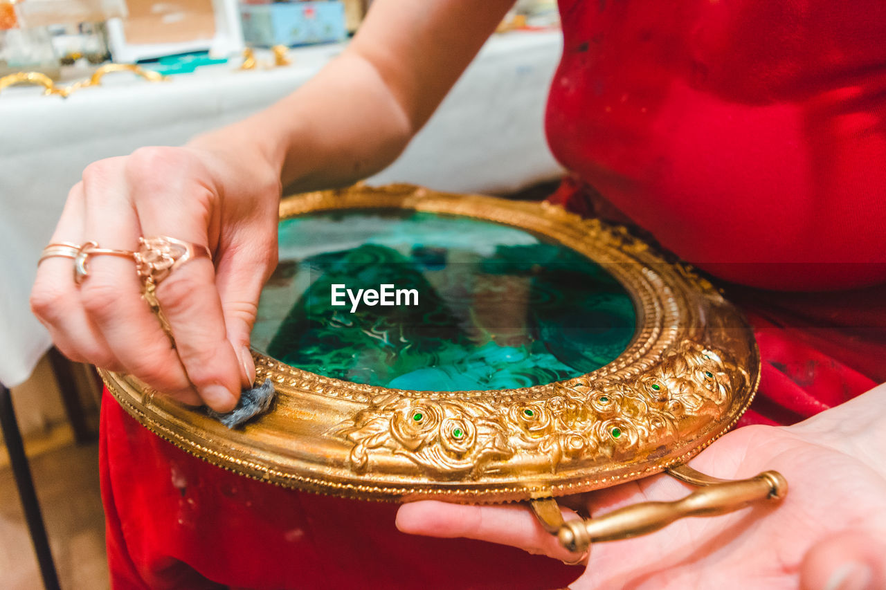 Midsection of woman decorating ornate container