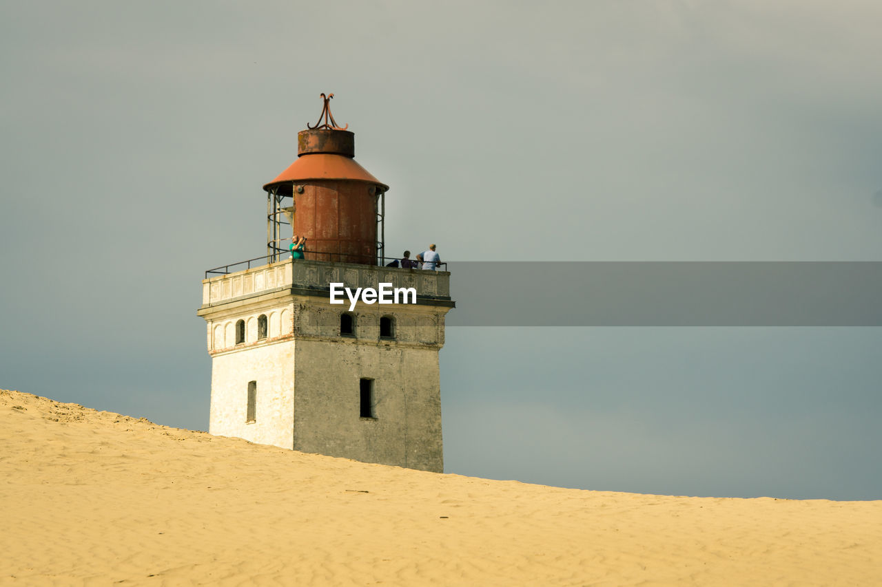 sand, architecture, lighthouse, sky, beach, built structure, sand dune, building exterior, outdoors, day, nature, no people, low angle view, beauty in nature