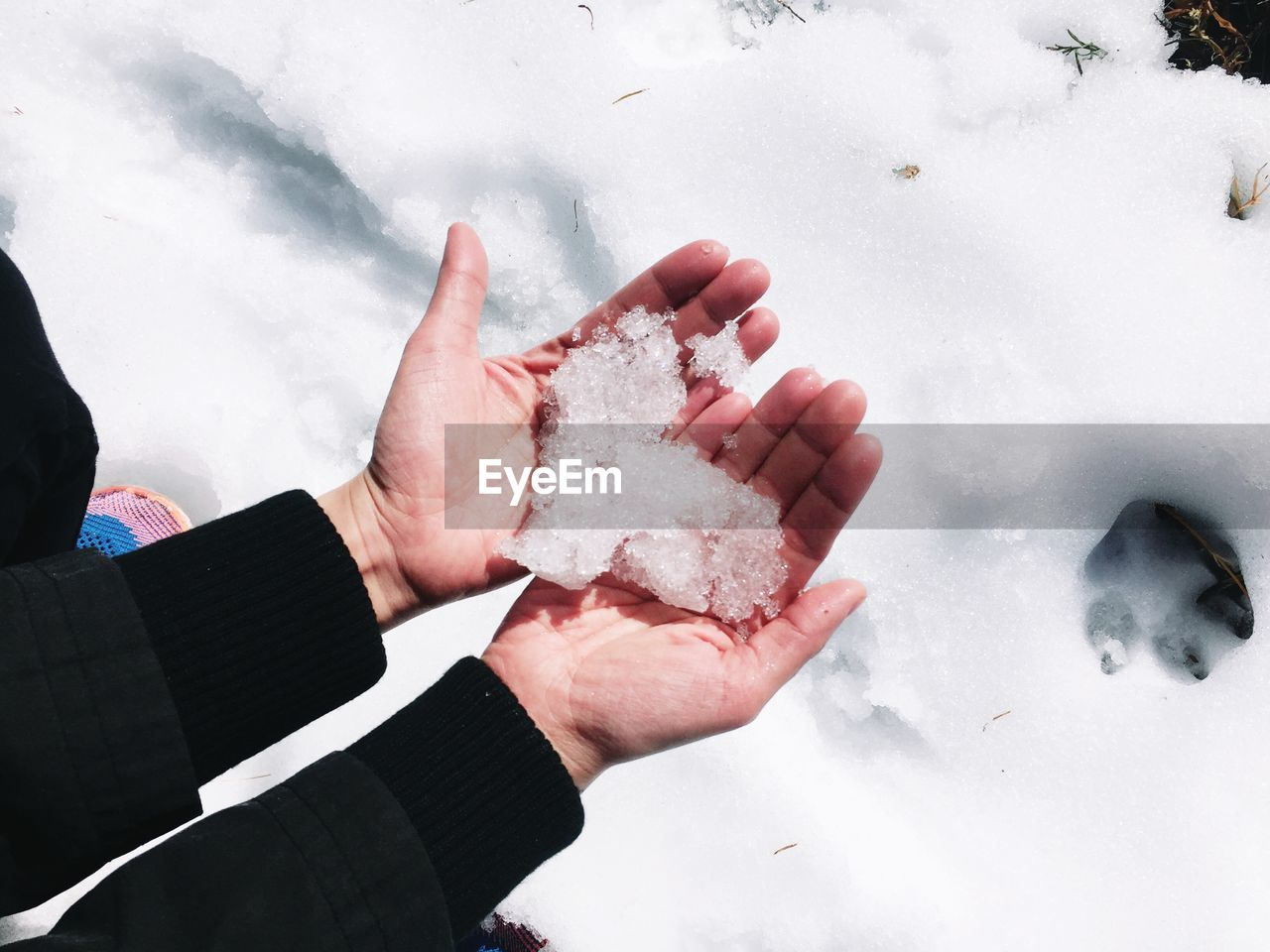 High angle view of human hands holding snow in heart shape during winter