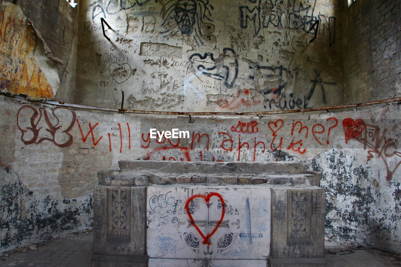 text, communication, architecture, western script, graffiti, no people, built structure, old, wall - building feature, abandoned, damaged, day, indoors, wall, building, sign, weathered, art and craft, emotion, deterioration, messy, floral pattern, ruined