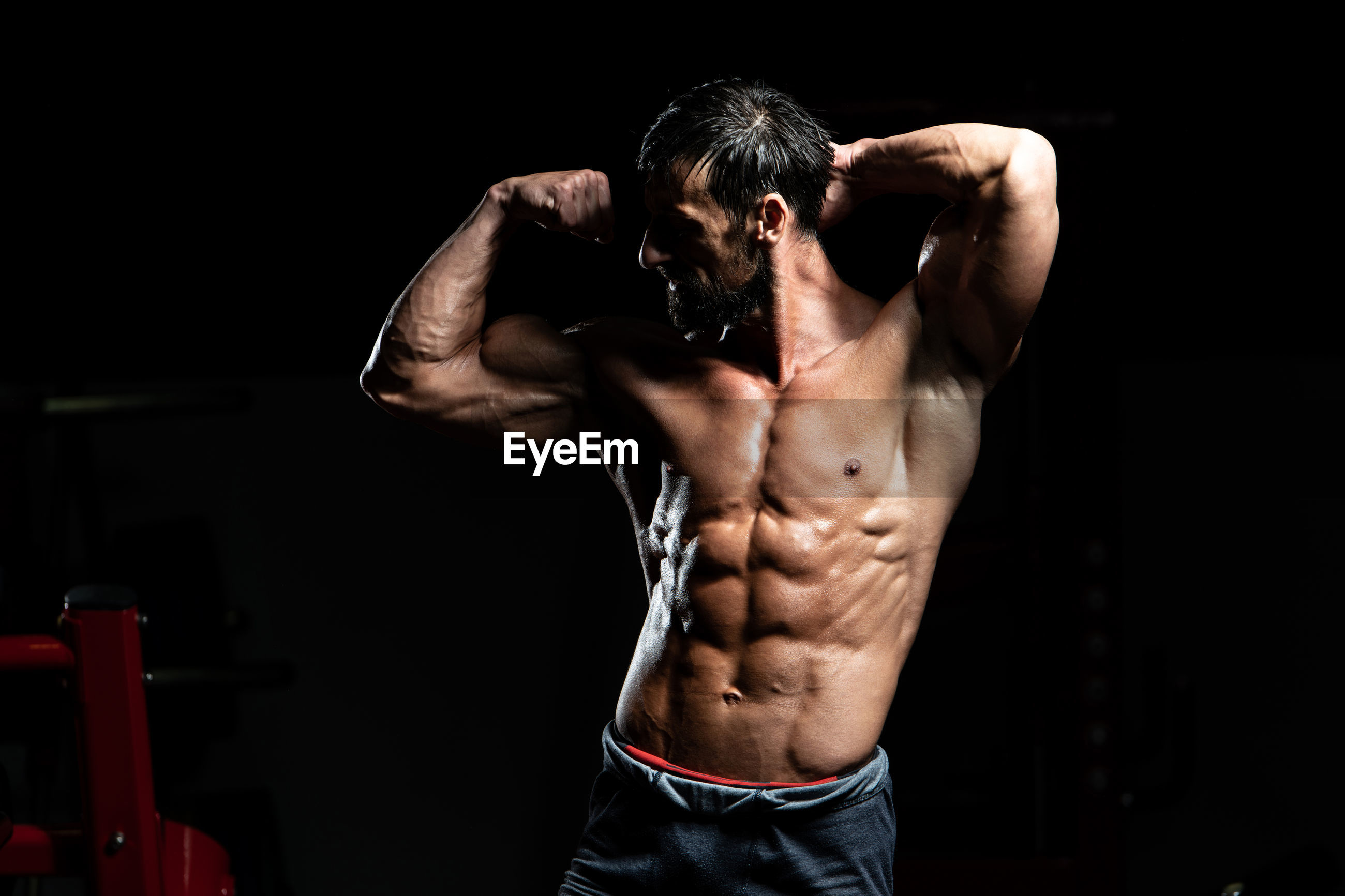 MIDSECTION OF SHIRTLESS MAN WITH ARMS OUTSTRETCHED