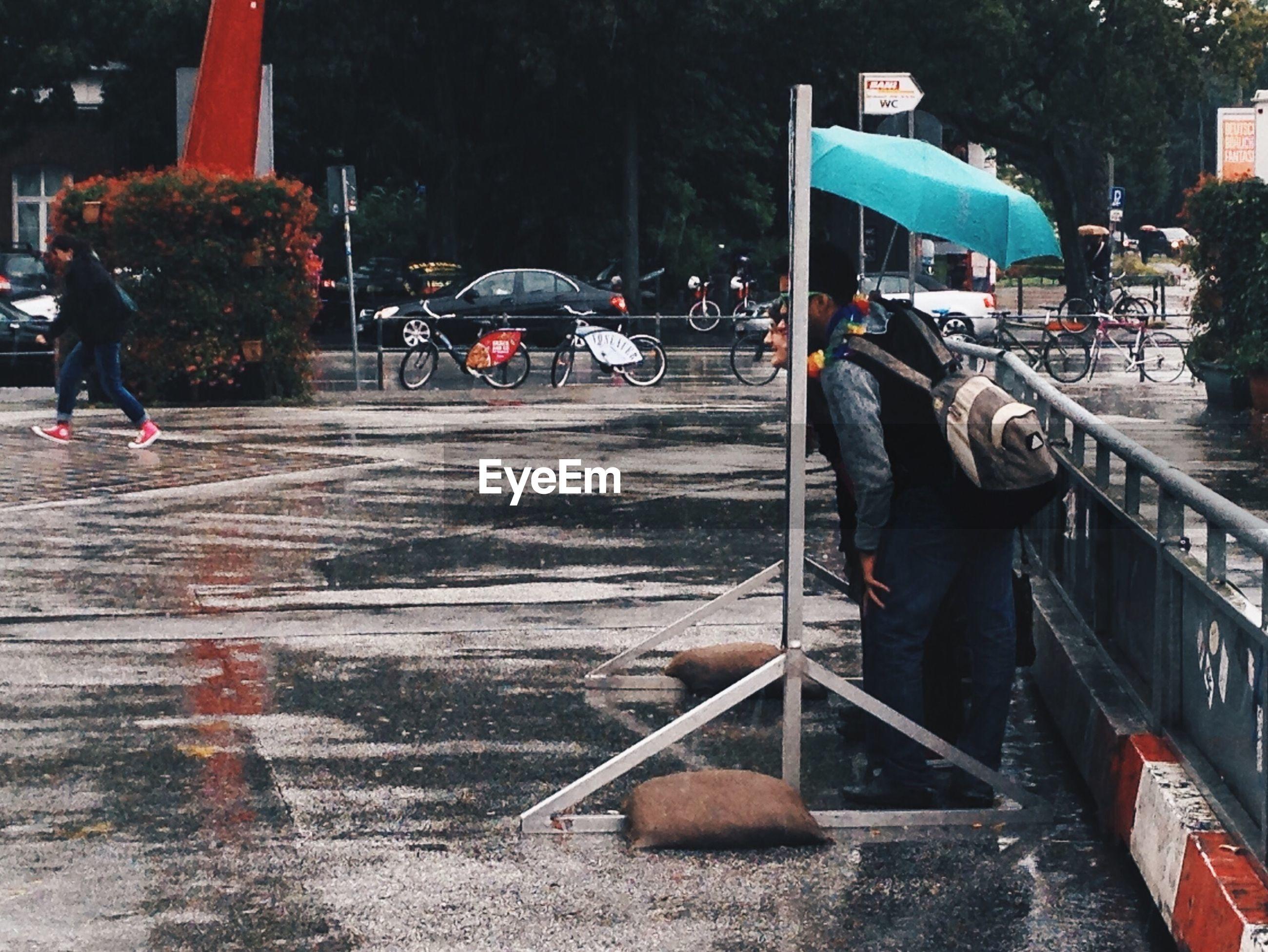 Men peeking through poster while standing on street during rainy season