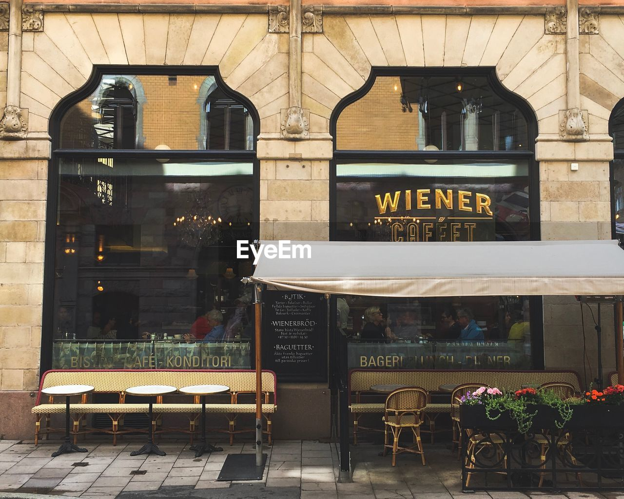 architecture, business, seat, building exterior, cafe, chair, built structure, restaurant, text, sidewalk cafe, window, glass - material, table, city, day, western script, communication, building, store, transparent, outdoors, coffee shop