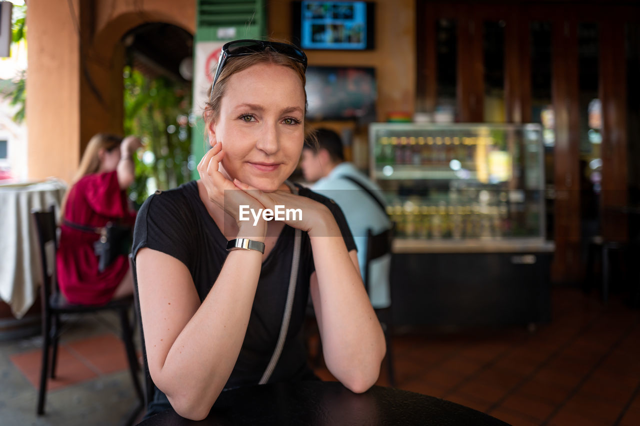 sitting, one person, real people, portrait, restaurant, women, lifestyles, looking at camera, leisure activity, indoors, young adult, focus on foreground, smiling, front view, table, business, females, adult, beautiful woman, hairstyle