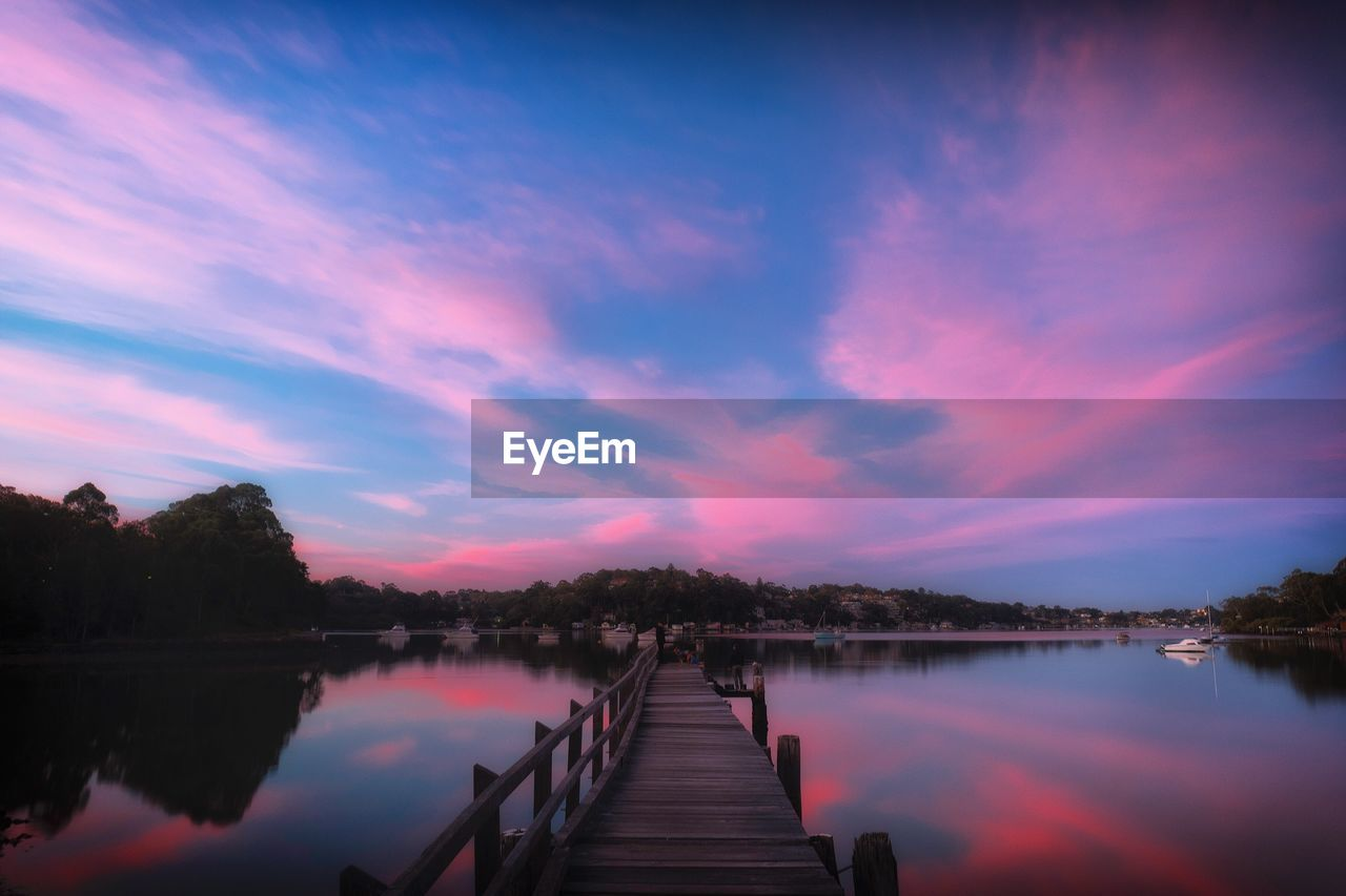 water, sky, lake, beauty in nature, cloud - sky, tranquility, reflection, scenics - nature, tranquil scene, pier, sunset, nature, wood - material, jetty, direction, the way forward, idyllic, tree, non-urban scene, outdoors, no people, diminishing perspective, wood paneling, purple