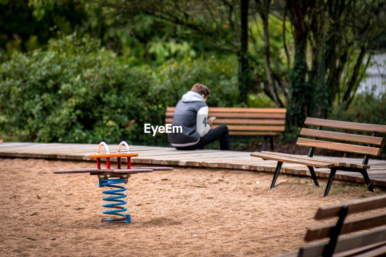 Spring Ride With Man In Background Sitting On Boardwalk At Playground