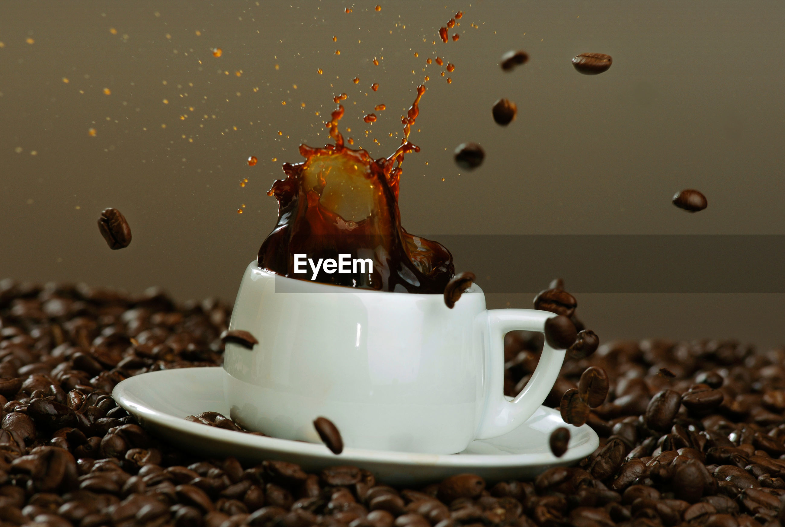 Roasted beans falling in coffee cup