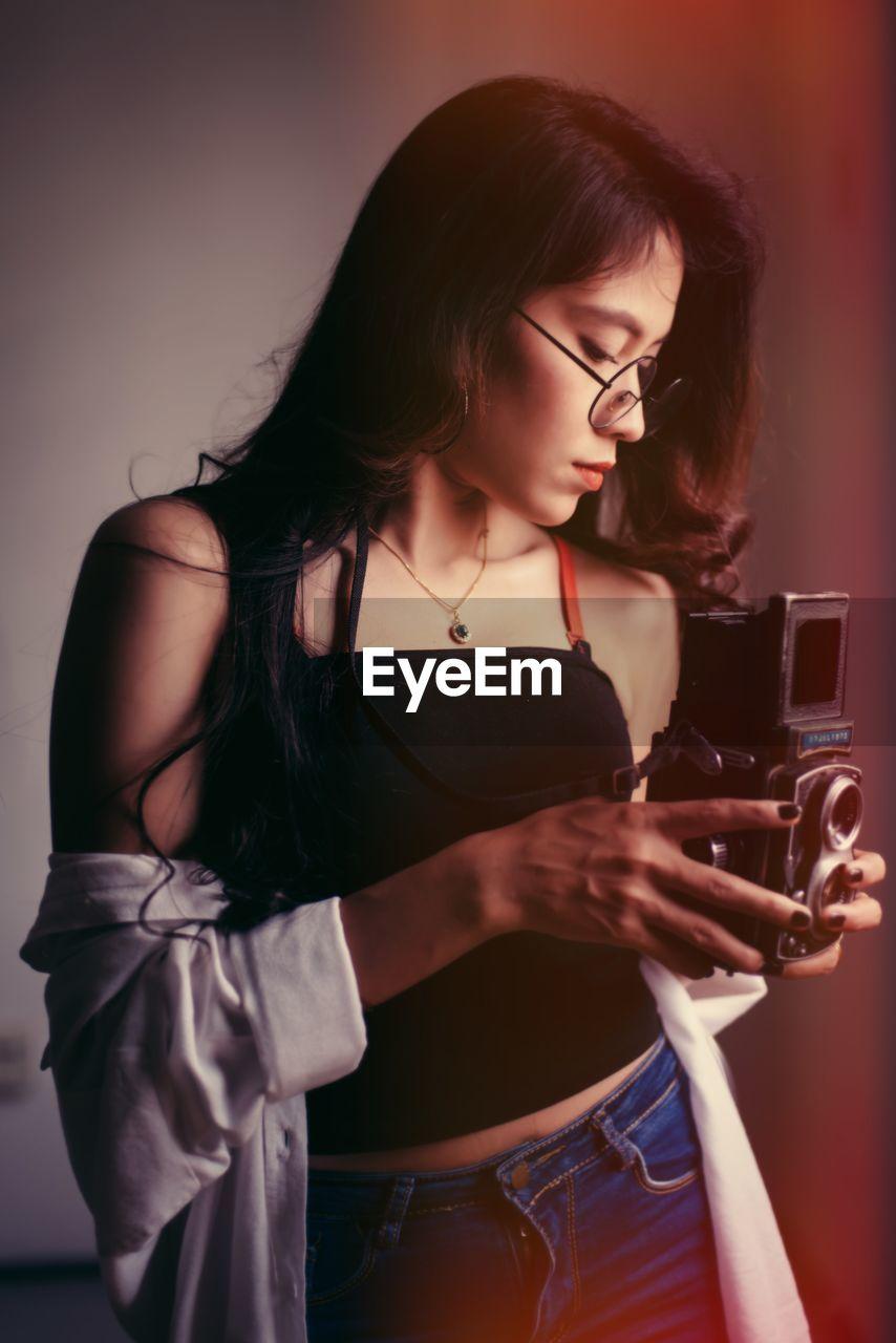 Young Woman Using Camera At Home
