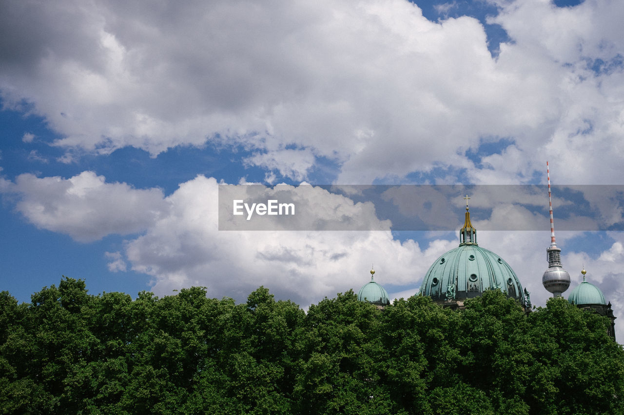 High Section Of Cathedral By Trees Against Cloudy Sky
