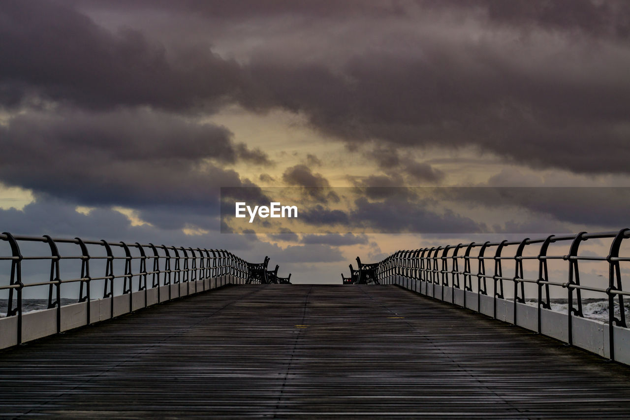 sky, cloud - sky, direction, the way forward, railing, sunset, nature, diminishing perspective, beauty in nature, connection, scenics - nature, bridge, built structure, architecture, pier, outdoors, overcast, tranquility, no people, footbridge, bridge - man made structure, long