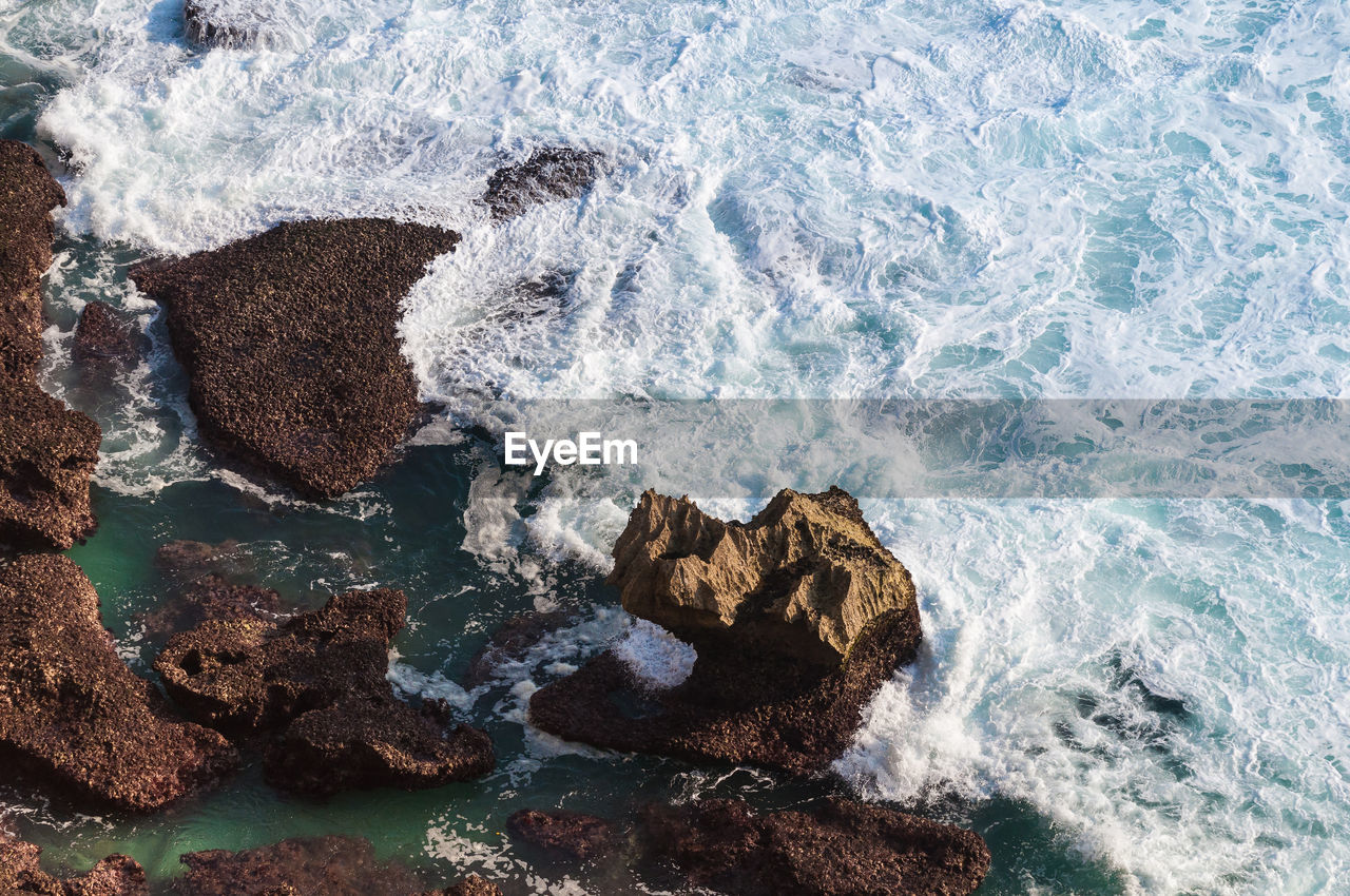 Aerial View Of Waves Splashing On Rocks In Sea