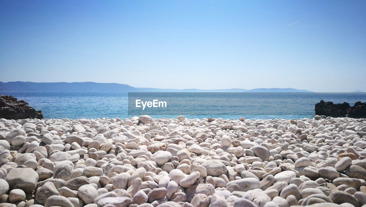 water, sky, sea, rock, scenics - nature, beach, solid, tranquil scene, tranquility, beauty in nature, clear sky, land, nature, day, copy space, rock - object, no people, stone, blue, pebble, outdoors