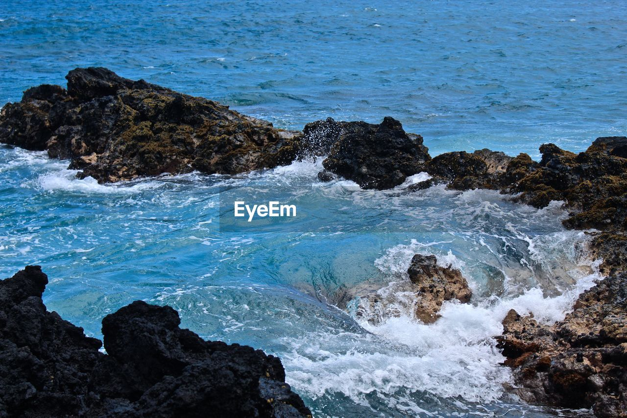sea, water, rock, beauty in nature, solid, rock - object, beach, land, sport, surfing, scenics - nature, aquatic sport, wave, motion, nature, day, splashing, rock formation, power in nature, outdoors, breaking, rocky coastline