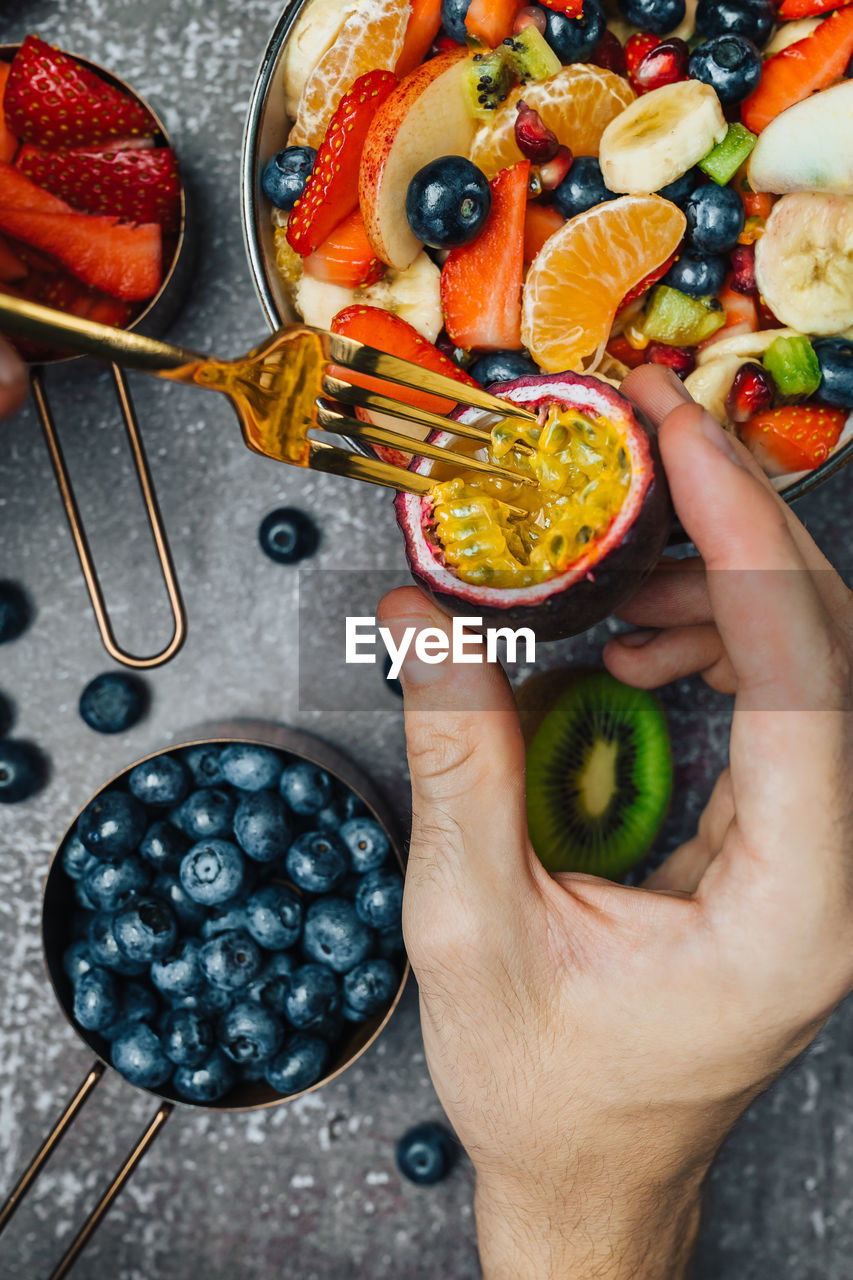 Overhead view of fresh fruits on table with hand holding passion fruit that is being eaten