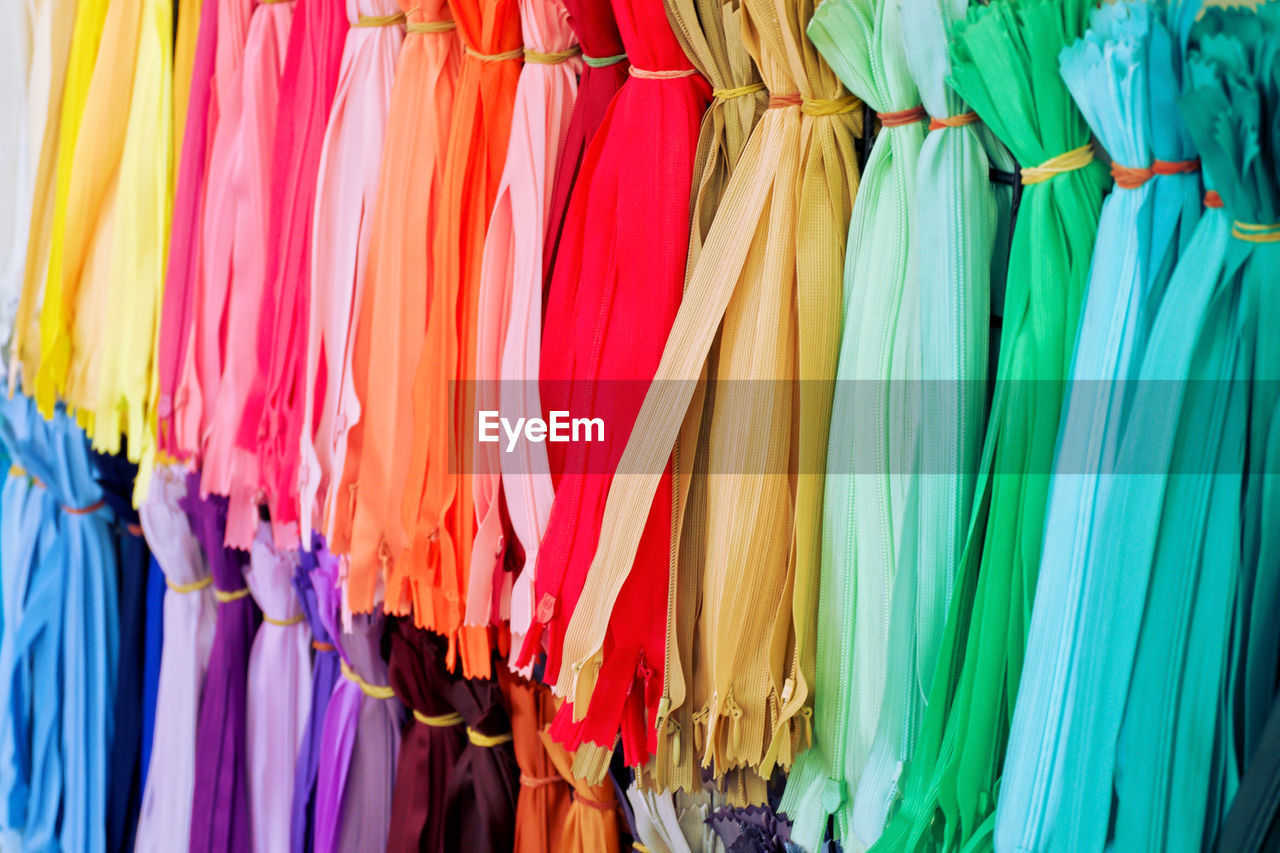 Full frame shot of multi colored zippers hanging at store