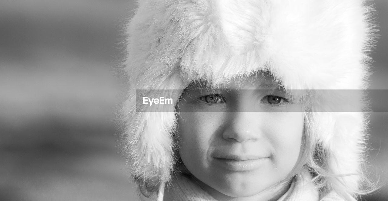 Close-Up Portrait Of Child In Fur Hat