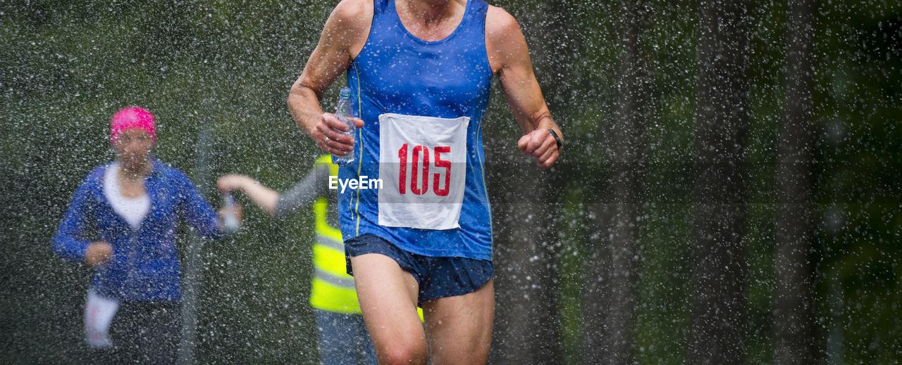 People running on wet street during rainy season
