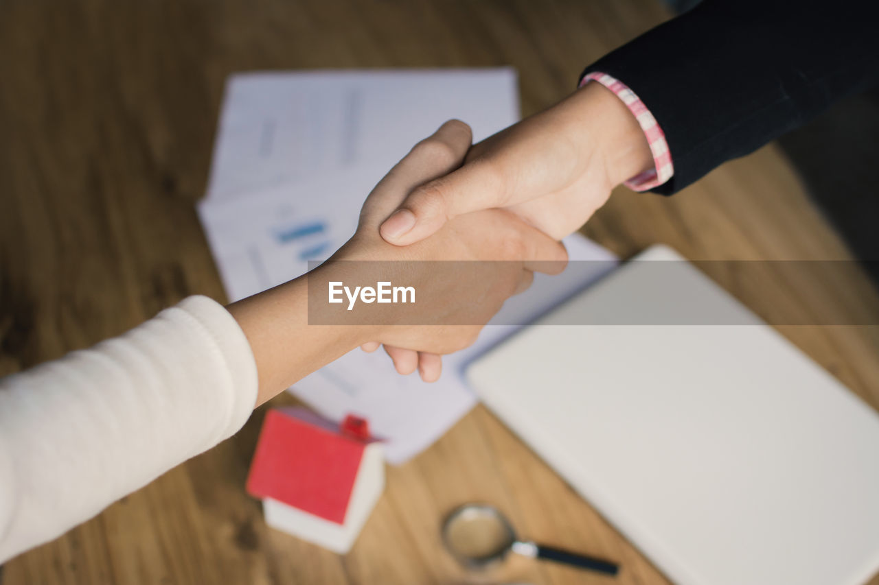 Cropped image of colleagues shaking hands over table
